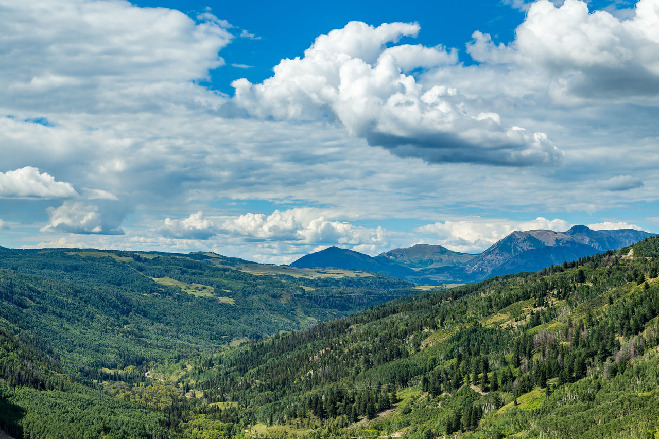 The San Juan Skyway forms a 233 mile loop in southwest Colorado traversing the heart of the San Juan Mountains festuring breathtaking mountain views and includes the portion of US 550 between Silverton and Ouray known as the Million Dollar Highway. Beauty In Nature Blue Cityscape Cloud - Sky Cloudscape Colorado Day Forest Green Color Landscape Lush Foliage Mountain Nature No People Outdoors San Juan Mountains San Juan Skyway Scenics Sky Social Issues Southwest  Southwestern Usa Tree Valley WoodLand