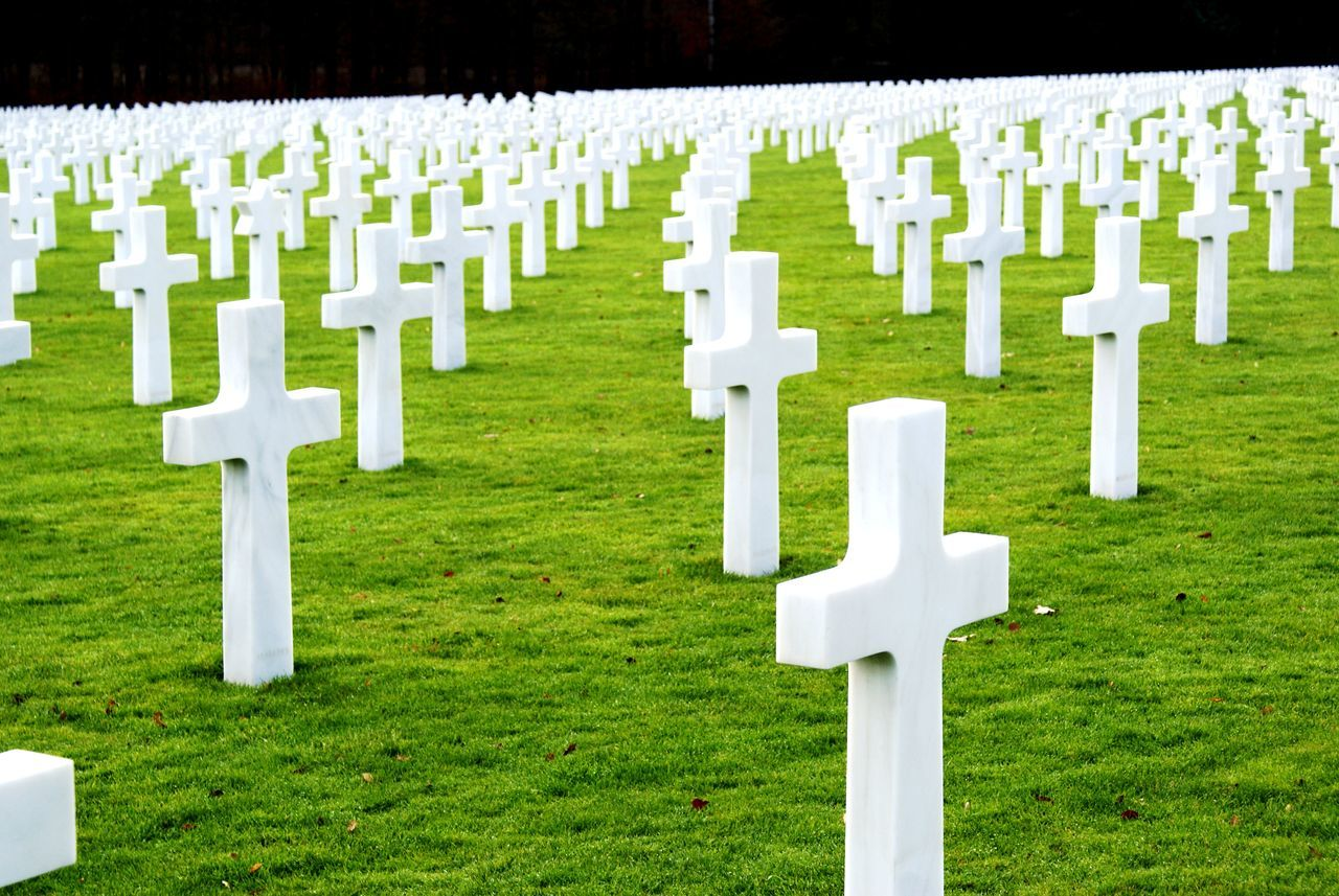 tombstone, cemetery, memorial, grass, grave, graveyard, gravestone, sadness, cross, in a row, green color, large group of objects, repetition, white color, day, no people, spirituality, respect, outdoors, war, military, nature