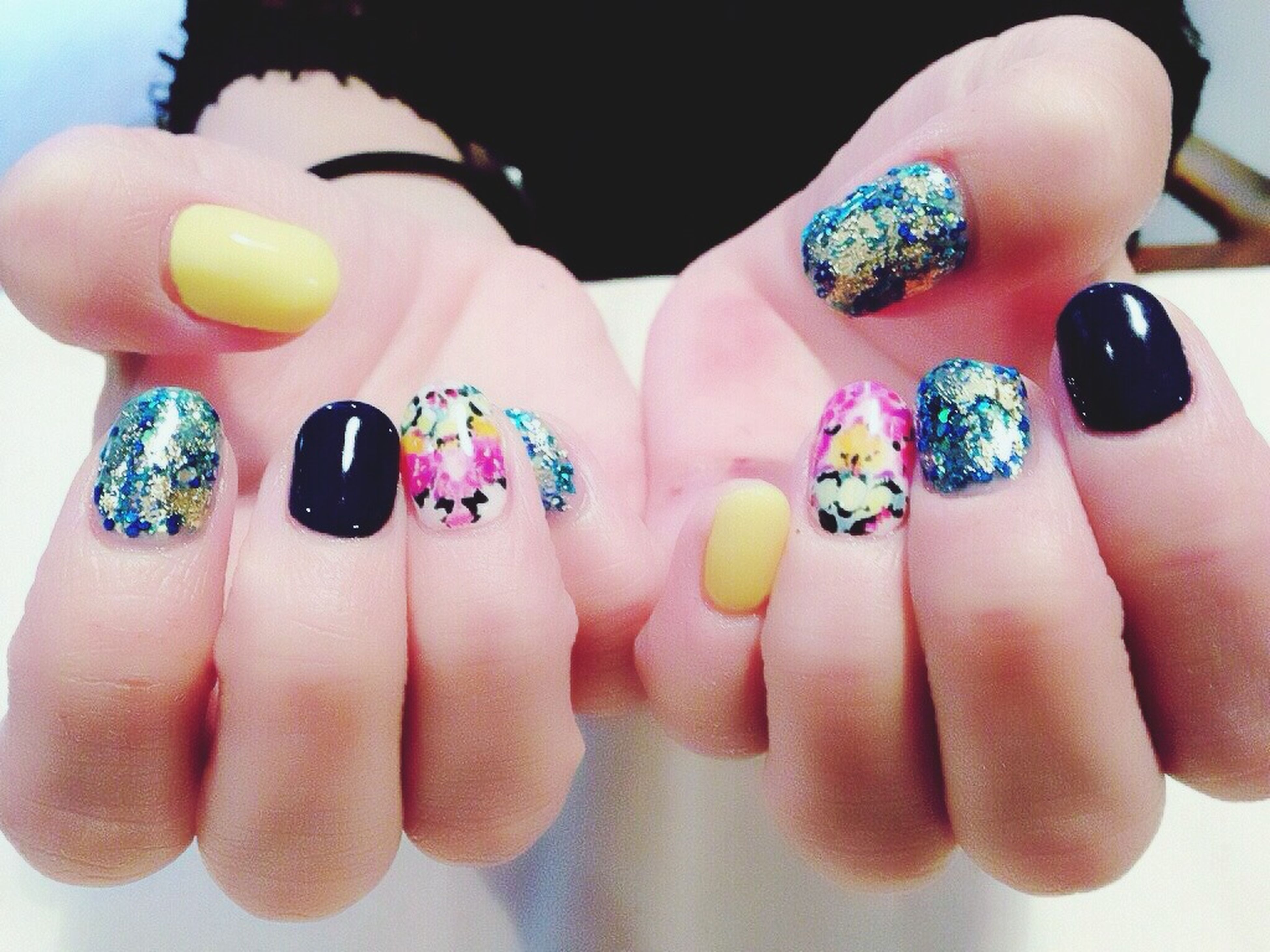 person, indoors, part of, holding, lifestyles, multi colored, leisure activity, human finger, food and drink, cropped, close-up, personal perspective, nail polish, high angle view, showing, variation