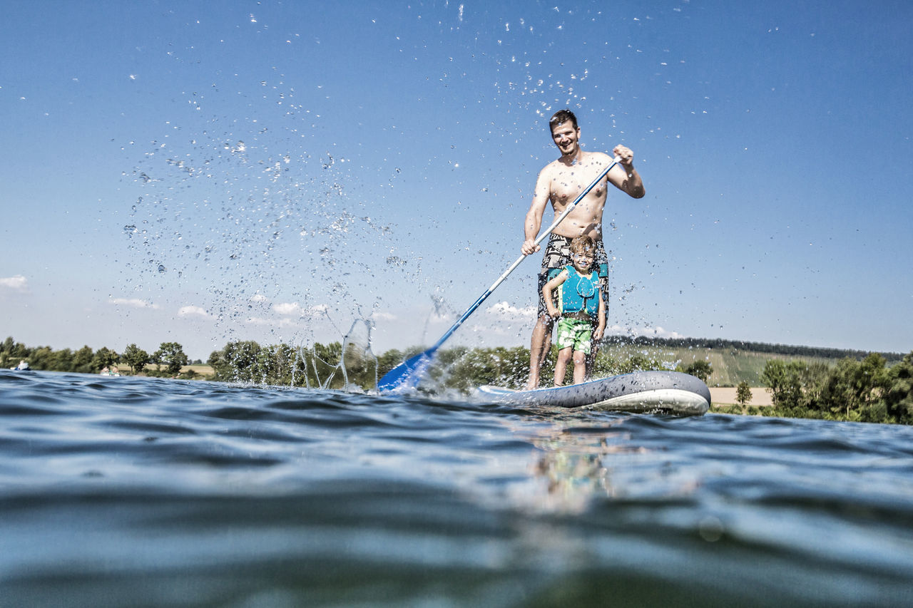 Father and son having fun on a standup paddleboard Baden-Württemberg  Bavaria Boy Carinthia Family Father Holiday Lake Leisure Activity Lifestyle Outdoors Over Under Paddle Recreation  Son Spending Time Splashing Standup Standup Paddleboarding Summer Sup Surf Togheterness Unfiltered Water