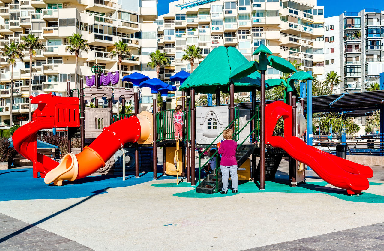 Marbella, Spain- January 8, 2014: Children playing in the playground in spanish resort city of Marbella. Province of Malaga, Andalusia, Costa del Sol. Southern Spain Area Children Family Lifestyle Malaga Marbella Palm Tree SPAIN Amusement  Child Childhood Costa Del Sol Entertainment Leisure Leisure Activity Outdoors Playful Playground Recreational Pursuit Slide - Play Equipment Sunny Day Tourist Resort Tropical Climate