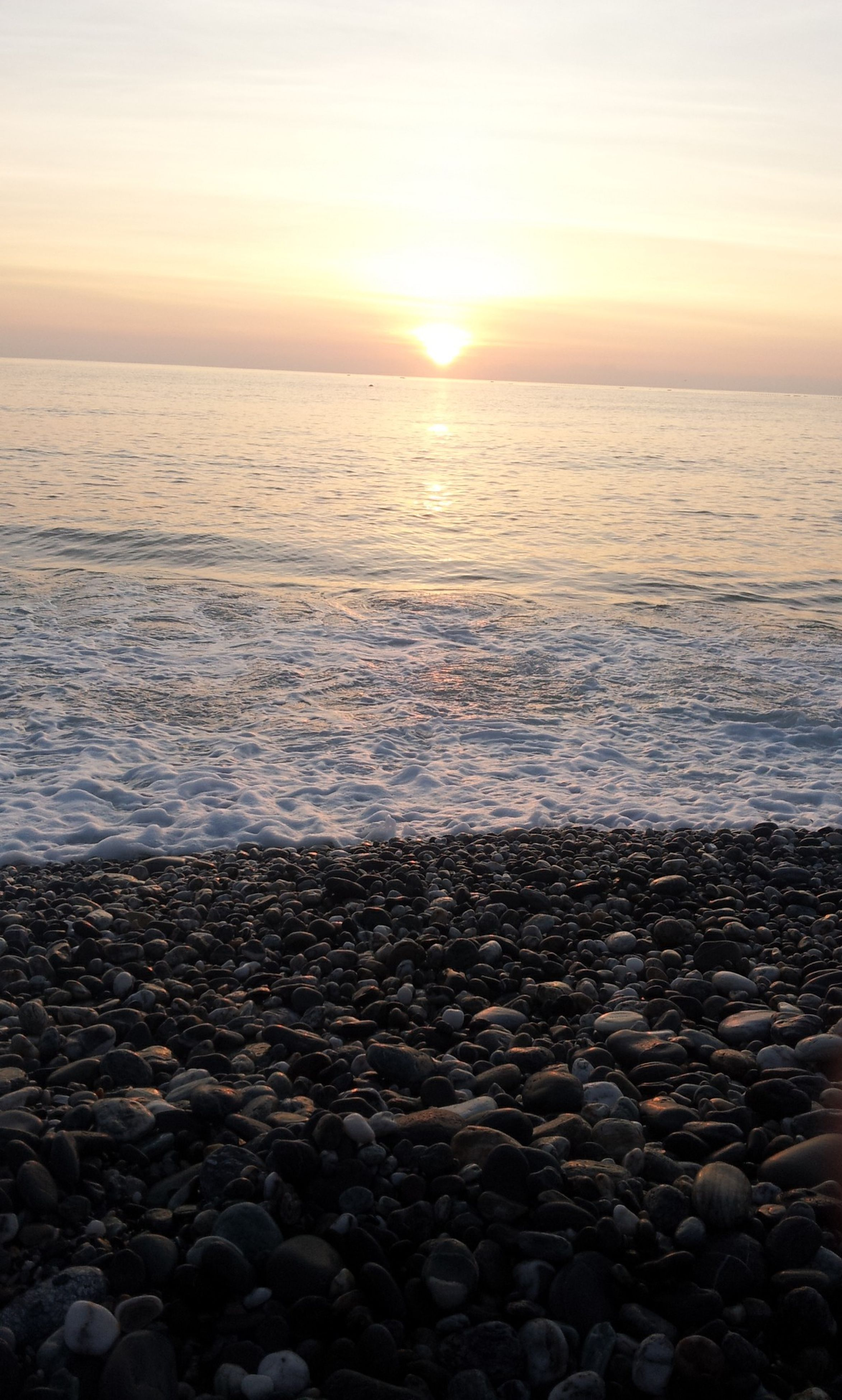 sea, water, horizon over water, sunset, scenics, tranquil scene, beach, beauty in nature, tranquility, sun, shore, nature, sky, idyllic, rock - object, stone - object, reflection, wave, seascape, sunlight