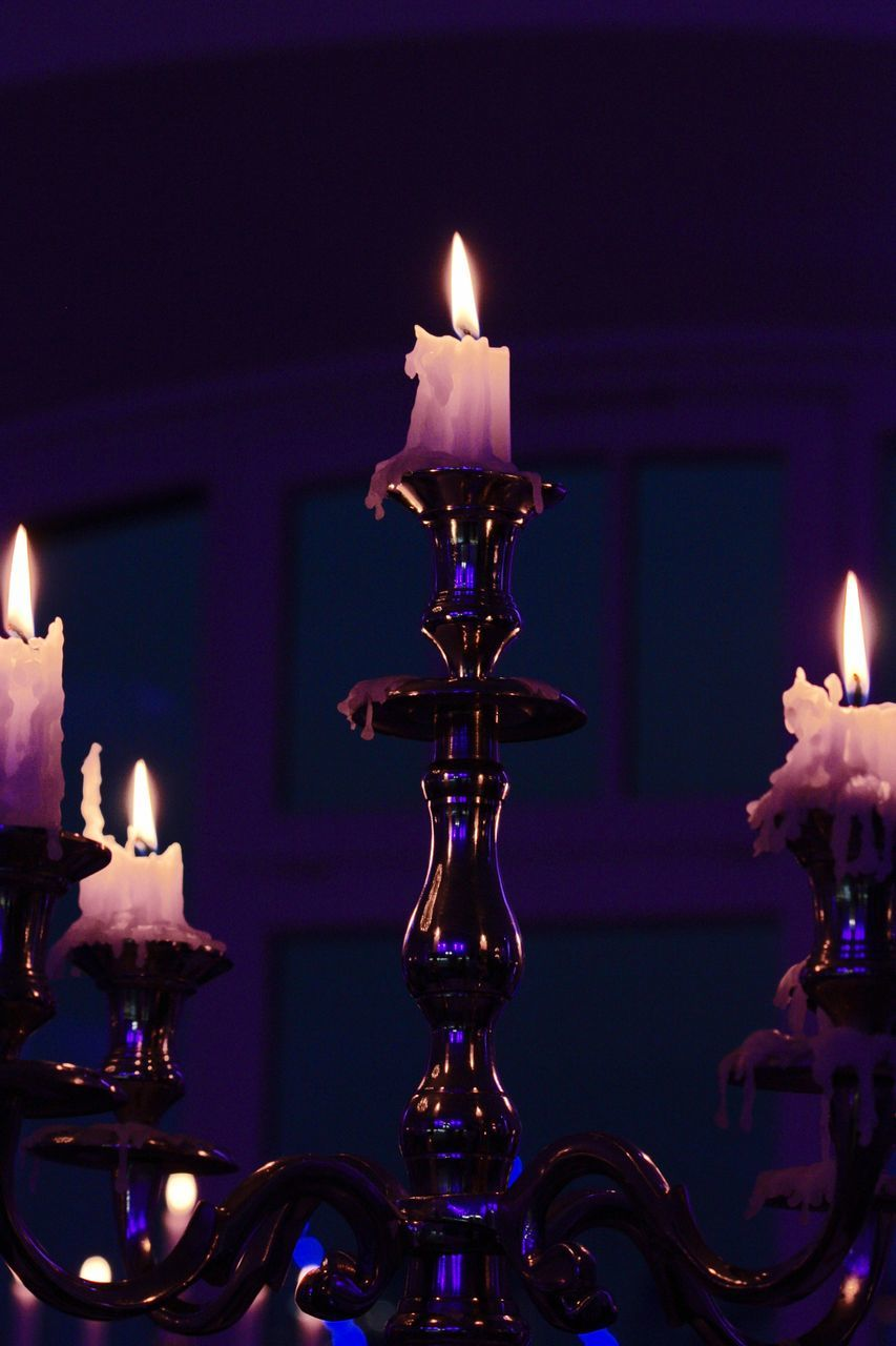 Close-Up Of Illuminated Candles On Candlestick Holder At Night