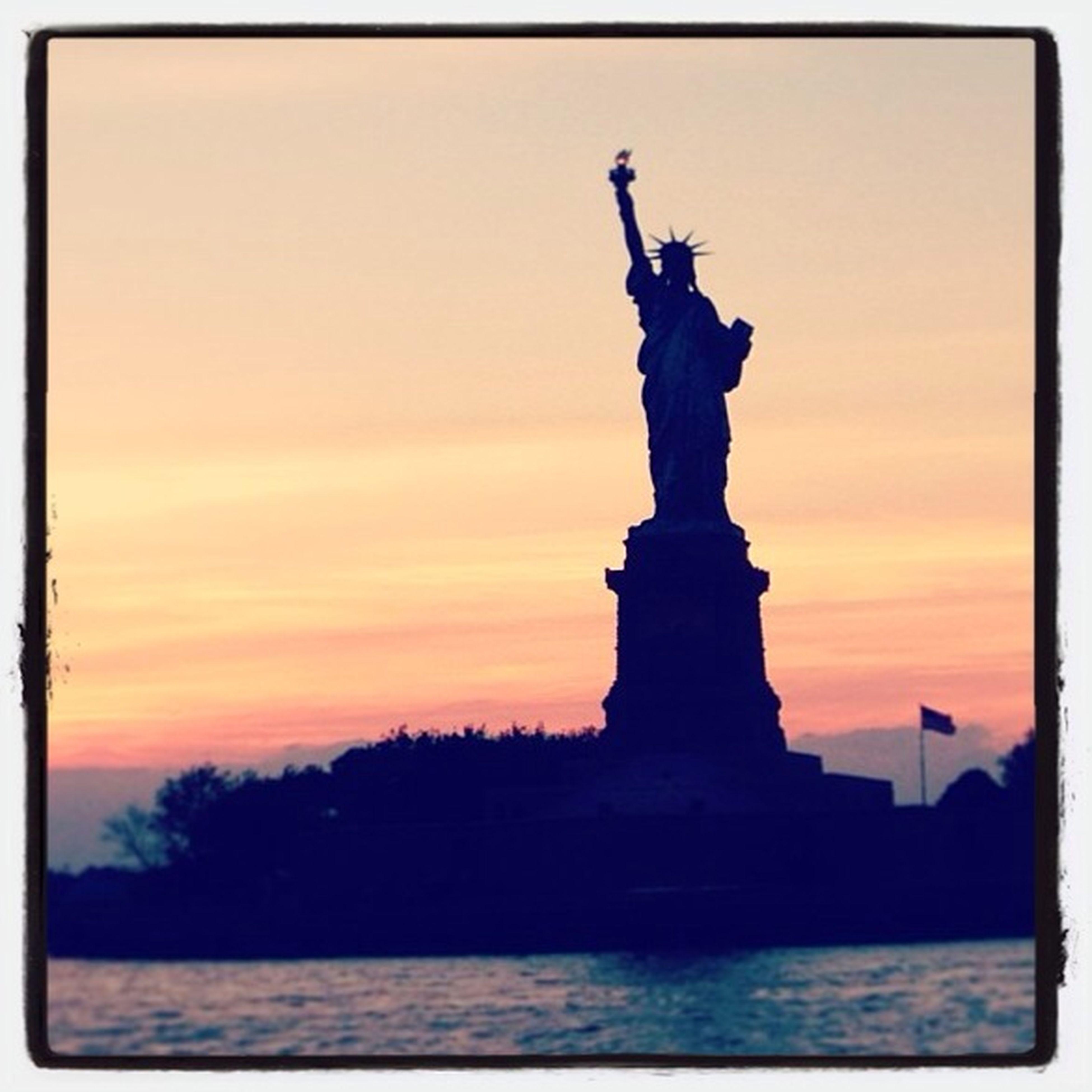 statue, sunset, human representation, sculpture, art and craft, art, creativity, transfer print, silhouette, sky, orange color, famous place, architecture, travel destinations, built structure, religion, auto post production filter, travel