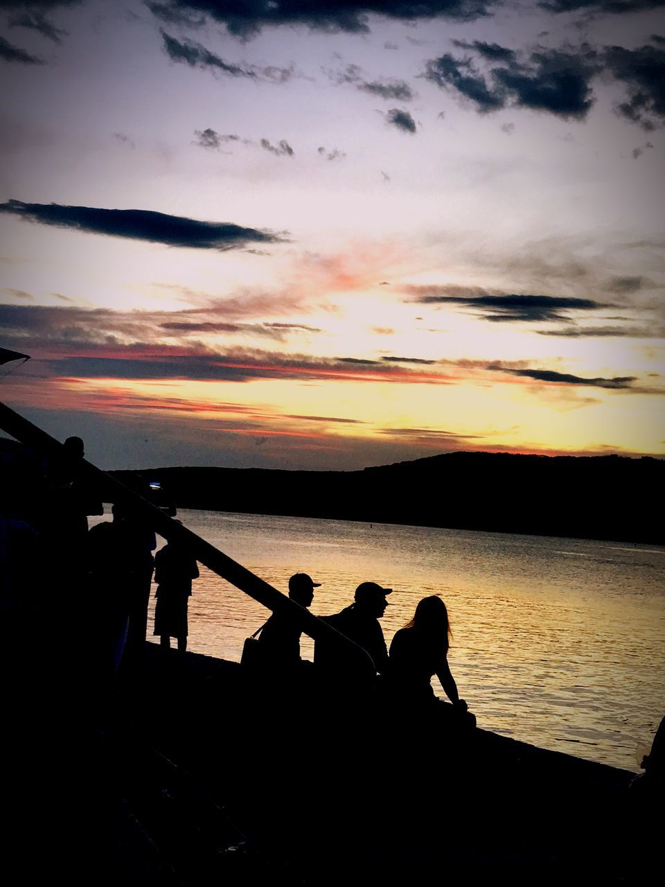 sunset, silhouette, water, sky, sitting, beauty in nature, nature, real people, cloud - sky, scenics, men, sea, leisure activity, outdoors, two people, togetherness, women, day, people