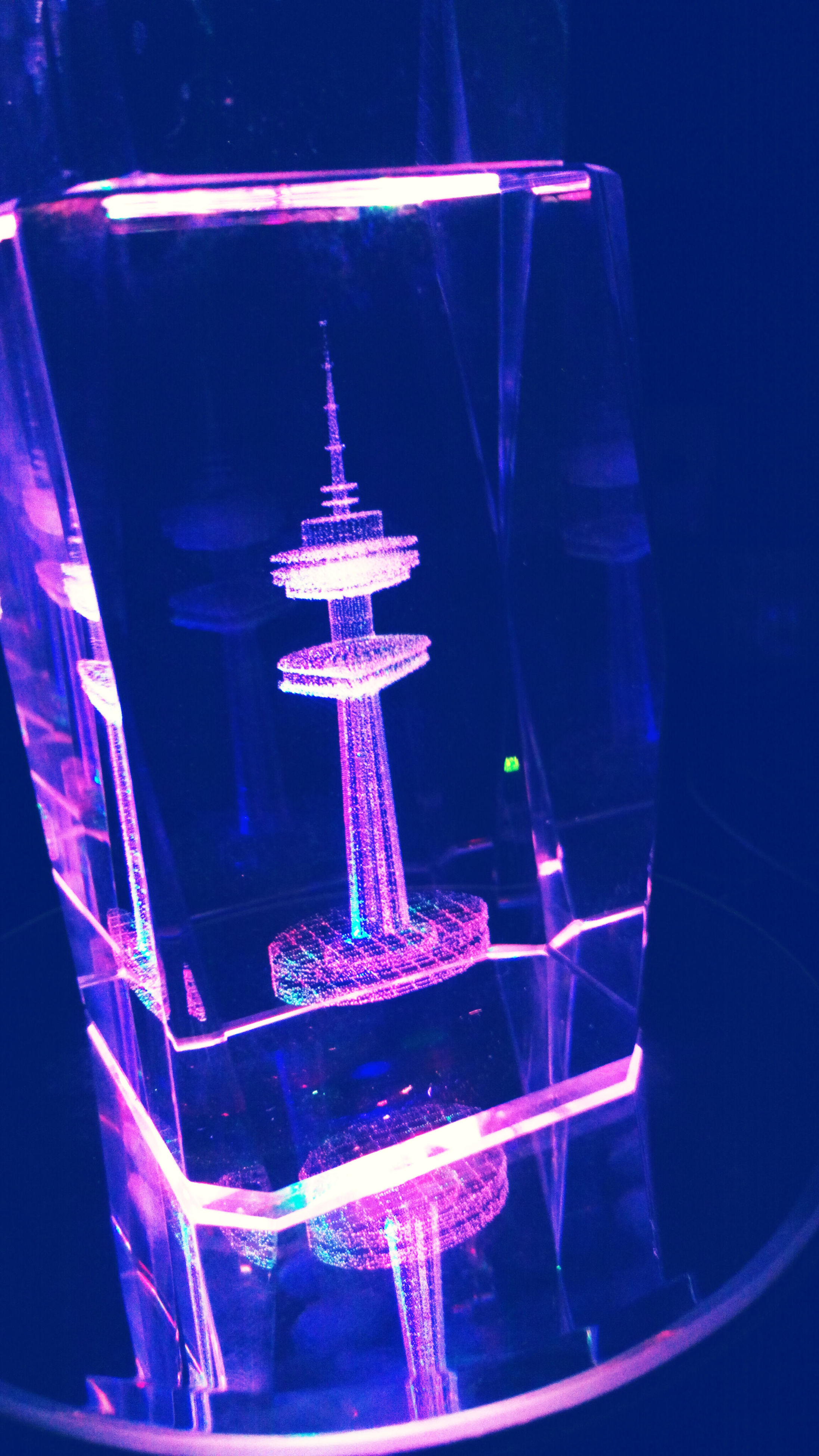 illuminated, night, low angle view, blue, architecture, glass - material, built structure, building exterior, lighting equipment, transparent, tall - high, tower, city, modern, glowing, light - natural phenomenon, indoors, no people, travel, sky