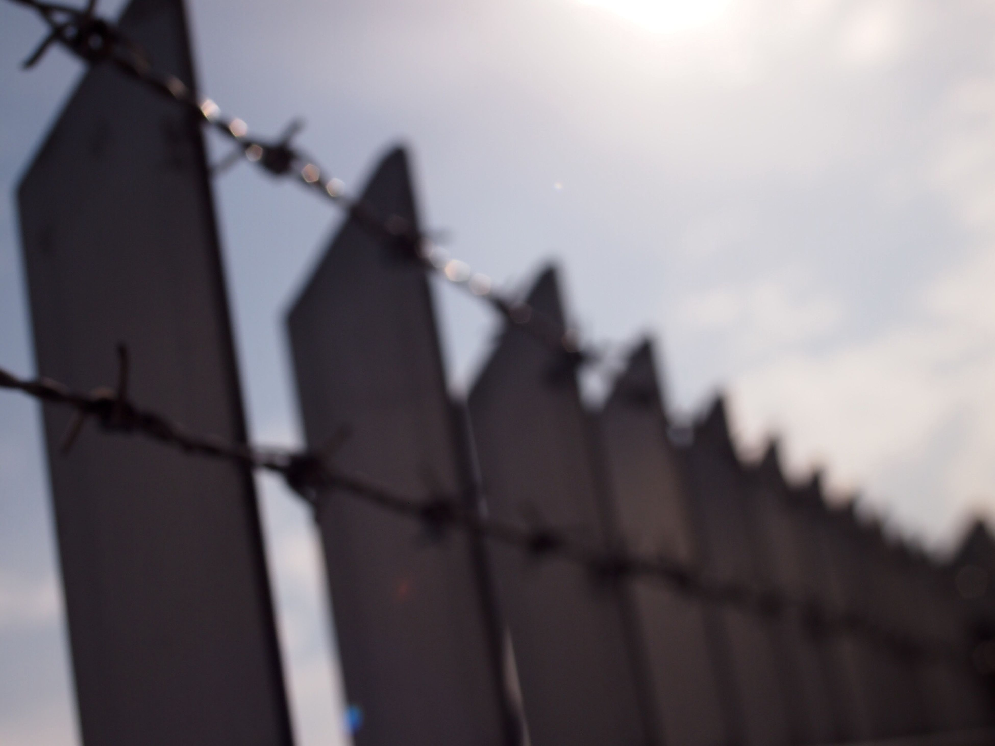 fence, protection, security, safety, focus on foreground, metal, chainlink fence, sky, close-up, barbed wire, low angle view, metallic, selective focus, in a row, pattern, day, outdoors, no people, hanging, nature