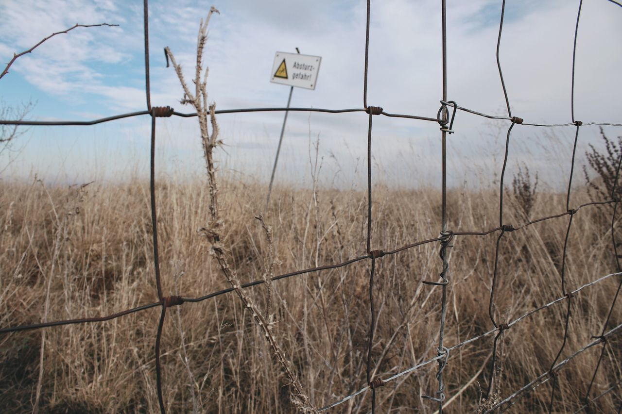 Fence No People Shield Sign Apocalypse Landscape Dry Grassland Tundra Beauty In Nature Yellow Grass Wastland  Autumn Steppe No Mans Land Flowers Border Fences Focus On Foreground Wide Field Sky Field Plant Grass
