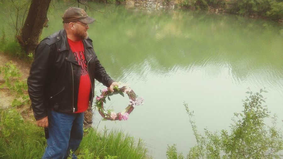 My friend's father throwing a wreath into the water where his son drowned up at the Nashua quarry in Iowa One Man Only Mature Adult One Person Adult Men Tradition River Outdoors Nature Day Life In Colors Beauty Beauty In Nature Water Nature Multi Colored Flowers In Bloom Silent Moment EyeEmNewHere