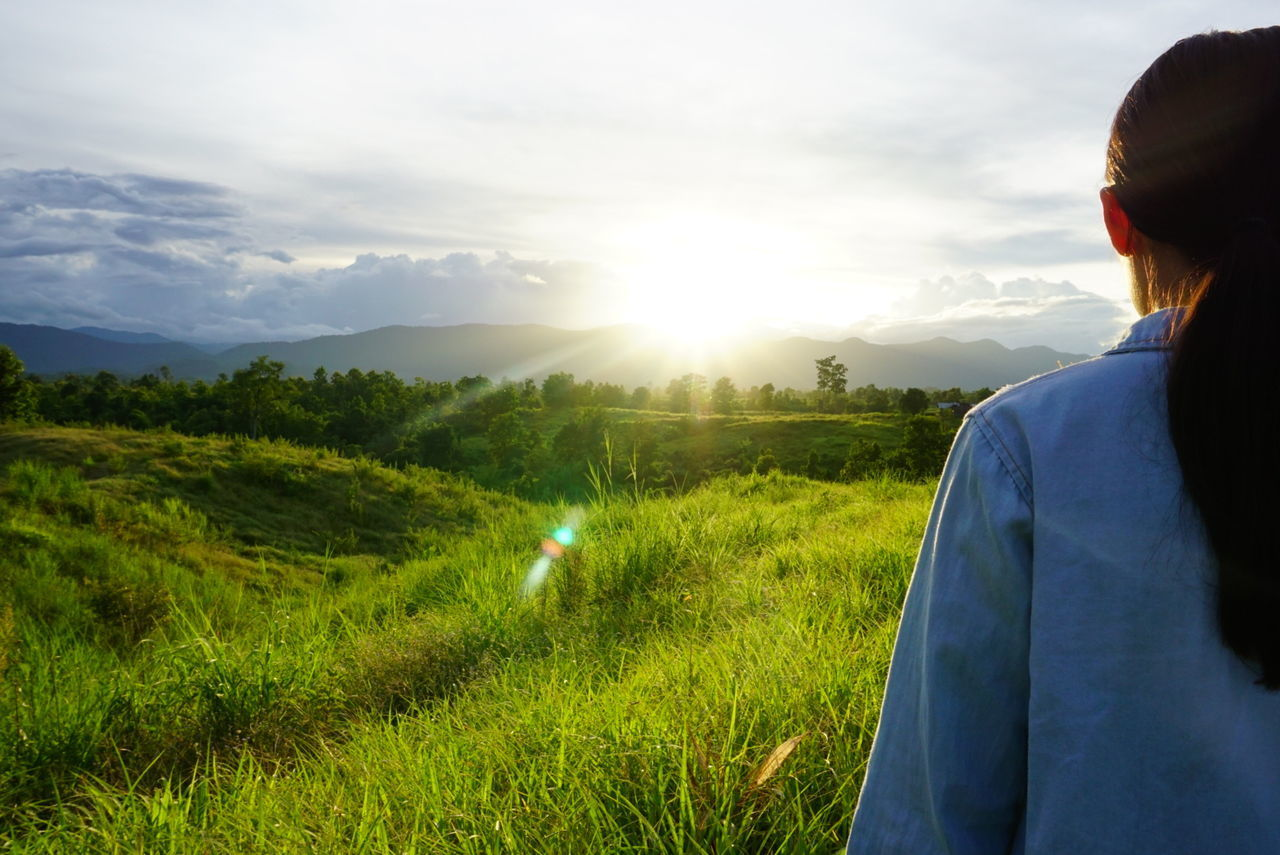 one person, real people, field, rear view, nature, leisure activity, sky, lifestyles, women, standing, outdoors, beauty in nature, sunset, landscape, grass, agriculture, growth, scenics, mountain, day, people