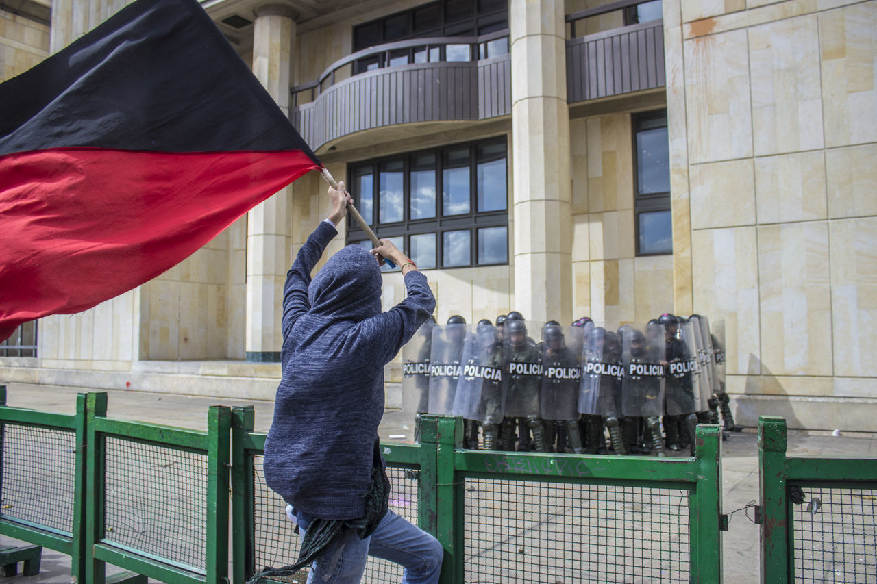 Protestor With Flag Against Building