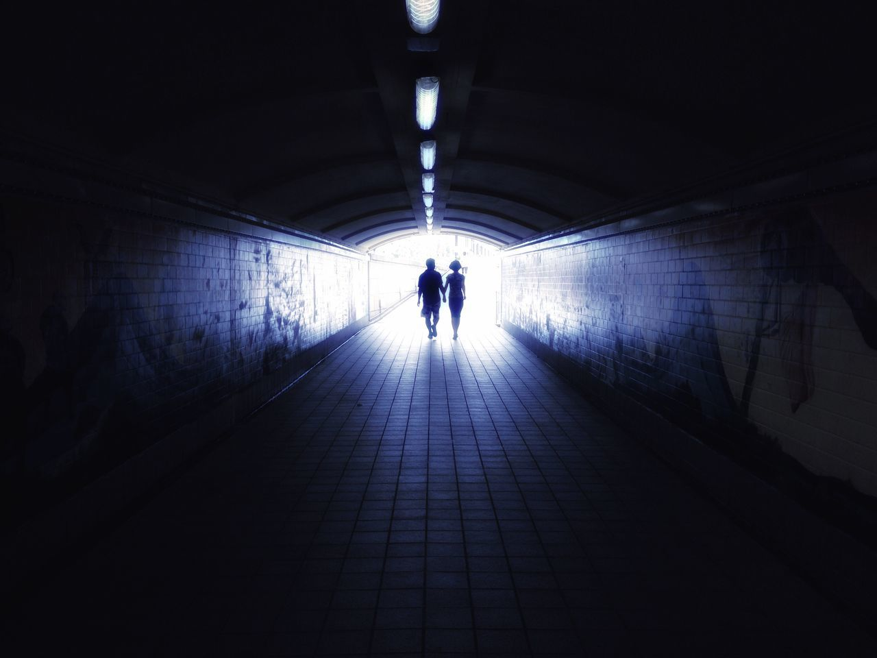 tunnel, real people, indoors, the way forward, illuminated, light at the end of the tunnel, full length, rear view, lifestyles, leisure activity, silhouette, architecture, built structure, two people, men, togetherness, women, day, adult, people