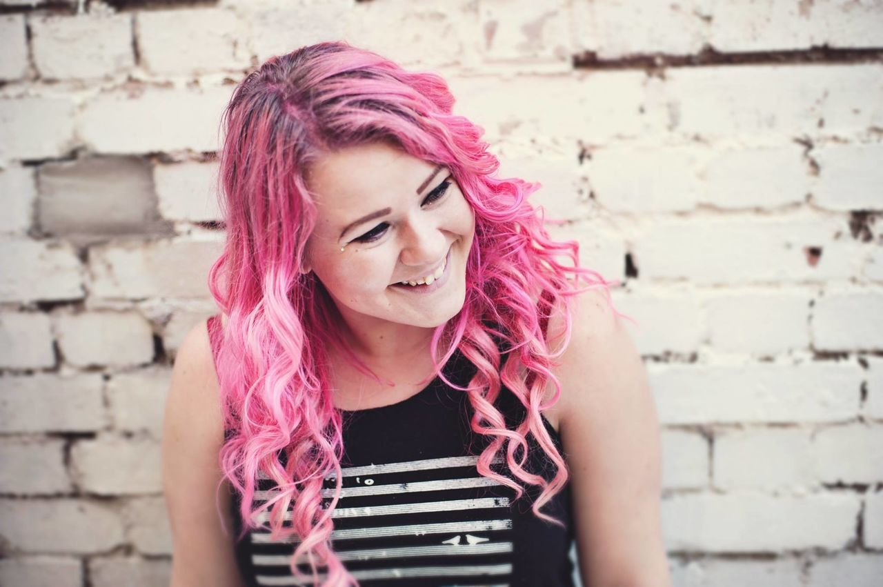 Adult Beautiful Woman Brick Wall Dyed Hair Fashion Happy London Looking Down One Person One Young Woman Only People Pink Color Portrait Punkrock Smiling Style Women Young Adult Young Women Youth Culture