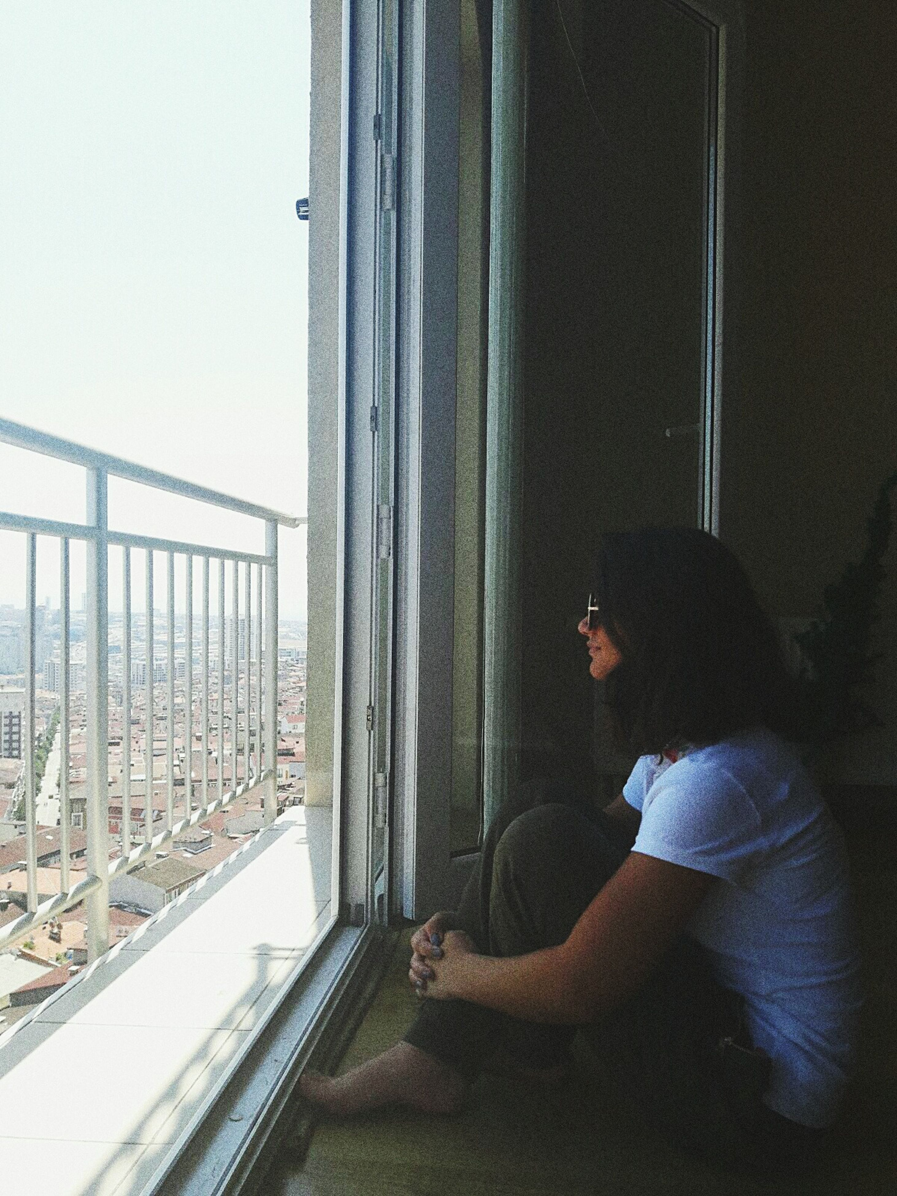 window, real people, looking through window, one person, young adult, indoors, side view, lifestyles, day, young women, architecture, built structure, sitting, technology, sky