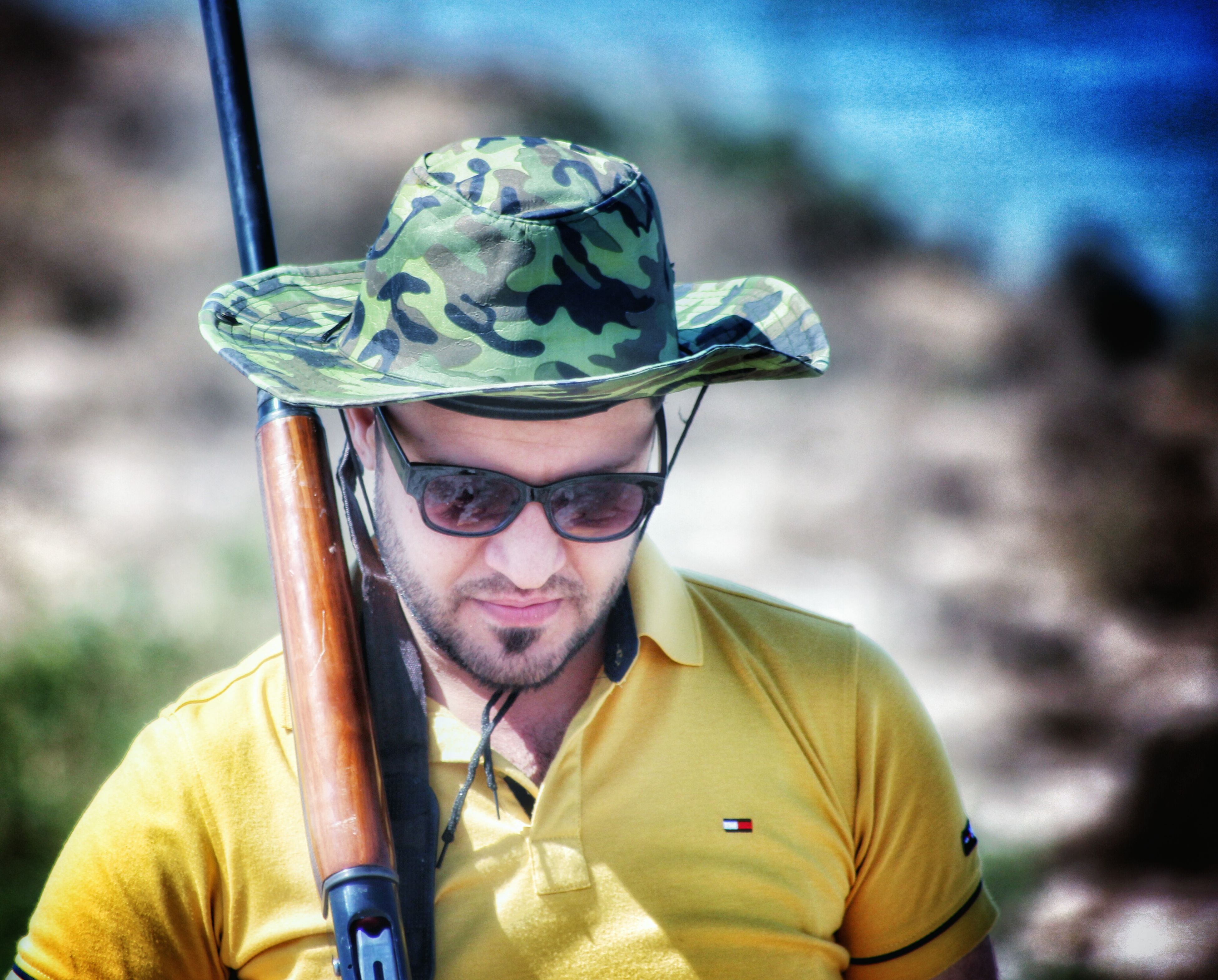 focus on foreground, headshot, lifestyles, person, close-up, leisure activity, portrait, looking at camera, front view, young adult, smiling, casual clothing, holding, waist up, head and shoulders, day, outdoors, hat