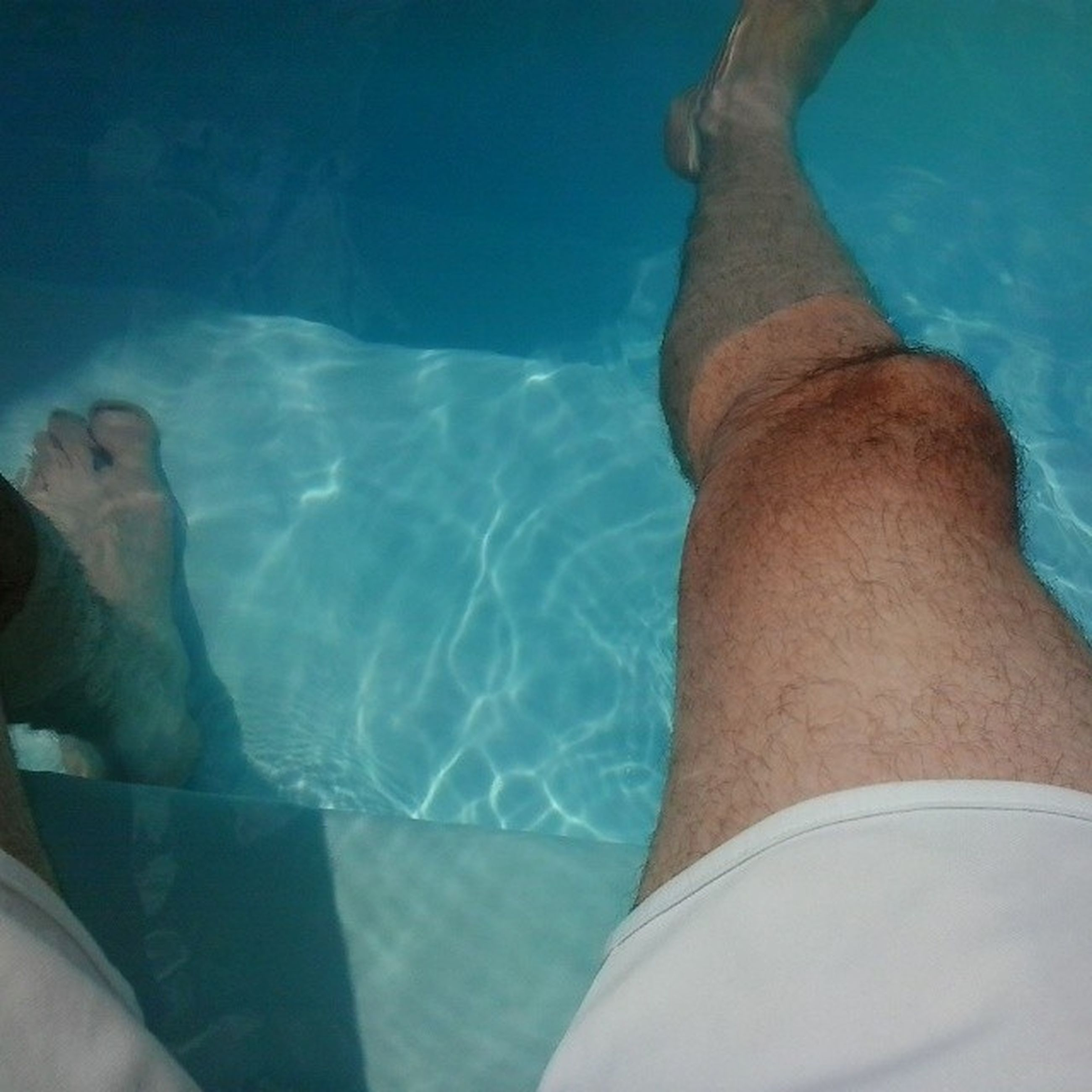 low section, person, lifestyles, leisure activity, blue, water, relaxation, swimming pool, personal perspective, part of, barefoot, indoors, men, human foot, high angle view