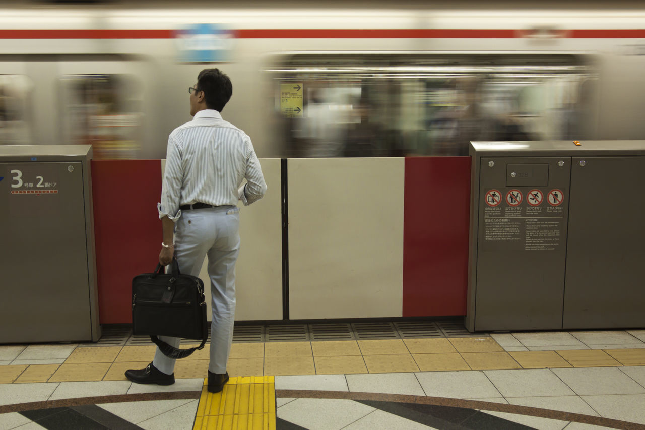 blurred motion, rear view, public transportation, real people, train - vehicle, motion, transportation, men, speed, railroad station platform, mode of transport, one person, railroad station, full length, rail transportation, standing, indoors, subway train, lifestyles, day
