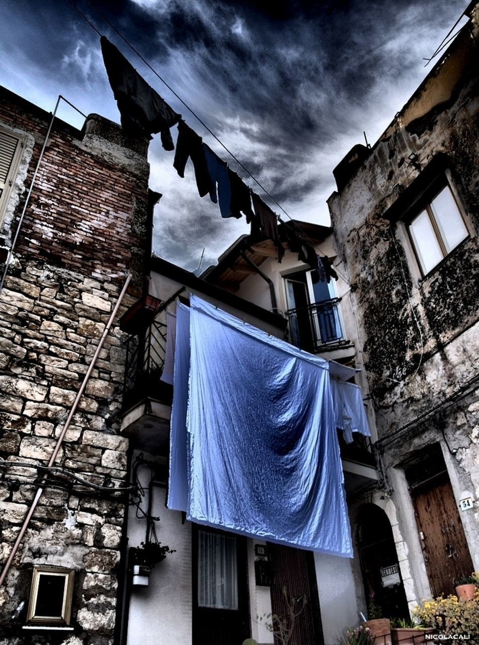 building exterior, architecture, drying, built structure, low angle view, clothesline, hanging, laundry, flag, window, house, residential building, textile, no people, day, outdoors, sky
