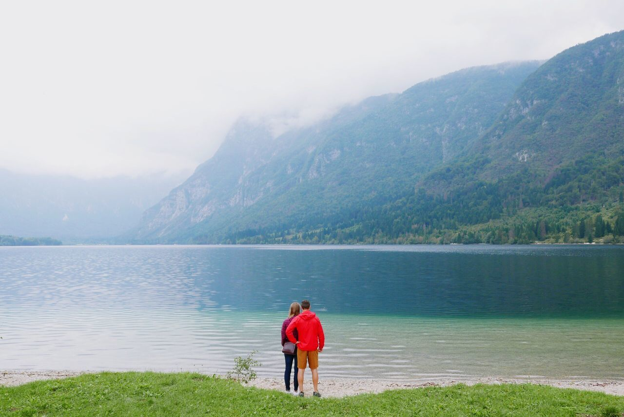 Two People Rear View Beauty In Nature Mountain Nature Togetherness Water Real People Scenics Full Length Leisure Activity Mountain Range Outdoors Day Lifestyles Standing Slovenia Lake