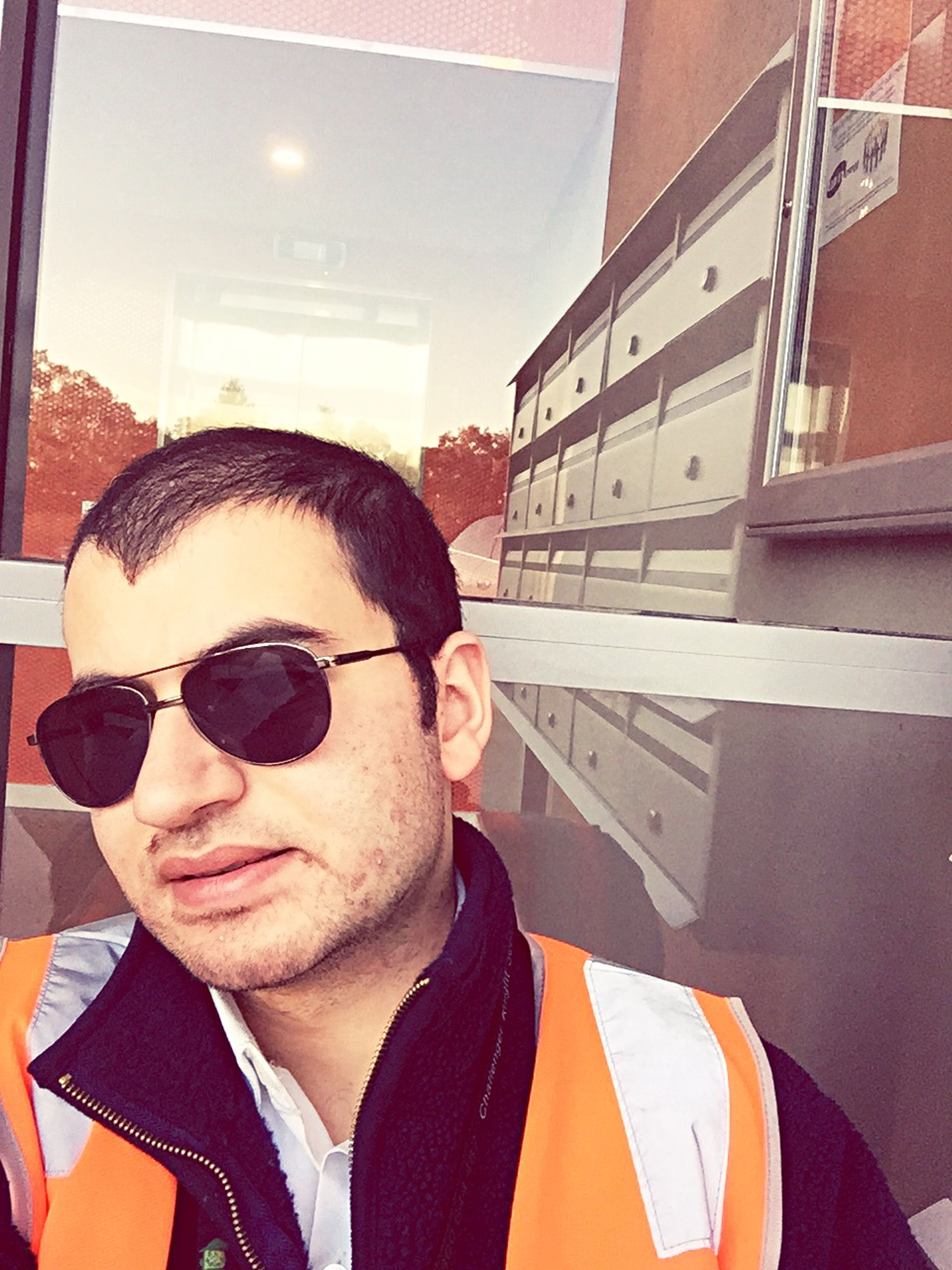 young adult, looking at camera, portrait, person, sunglasses, lifestyles, young men, headshot, front view, leisure activity, smiling, architecture, casual clothing, mid adult, mid adult men, building exterior, built structure