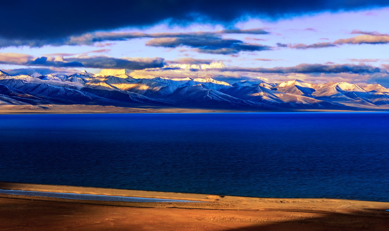 Snow covered mountain and Nam lake at sunrise, Tibet, China Beauty In Nature Blue Cloud - Sky Cold Temperature Day Lake Landscape Mountain Mountain Range Namtsolake Nature No People Outdoors Scenics Sky Snow Sun Sunrise Tibet Tranquil Scene Tranquility Travel Destinations Water Winter