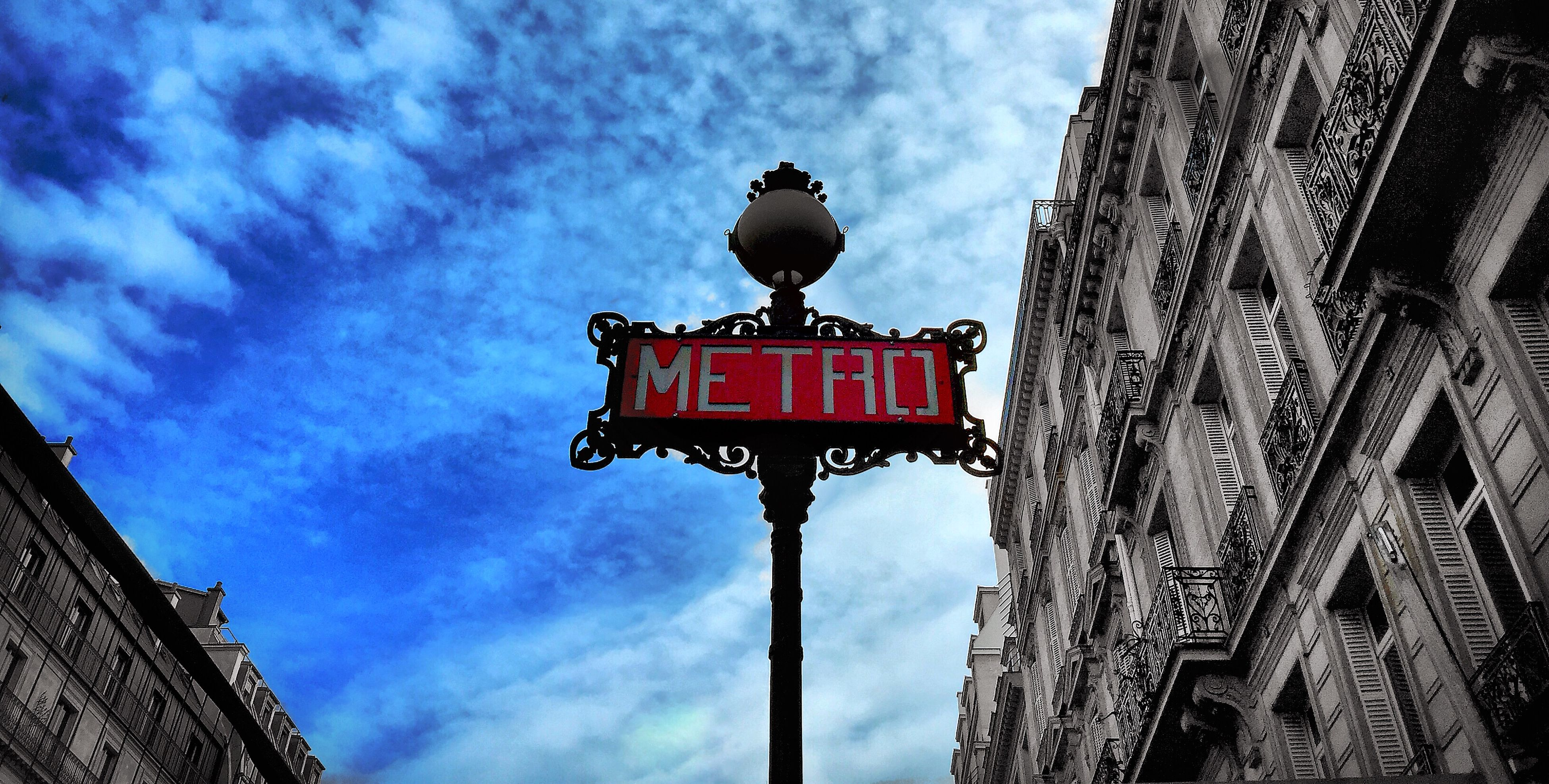 low angle view, architecture, building exterior, built structure, sky, cloud - sky, cloud, cloudy, red, lighting equipment, street light, city, outdoors, no people, high section, day, building, pole, blue, guidance