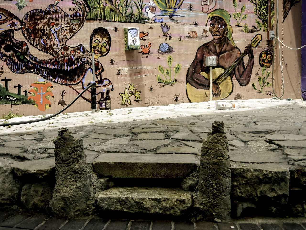 """An urban patio area featuring a tropical-styled, hand-painted mural on building wall. Depictions include a man playing guitar, tropical flora & fauna, and preternatural """"spirit"""" following the sound of music. Art Art, Drawing, Creativity Creativity Culture Day Full Frame Mural Outdoors Painting Patio Stone Stones Textured  Tropical Urban Art Urban Landscape Wall Weathered"""