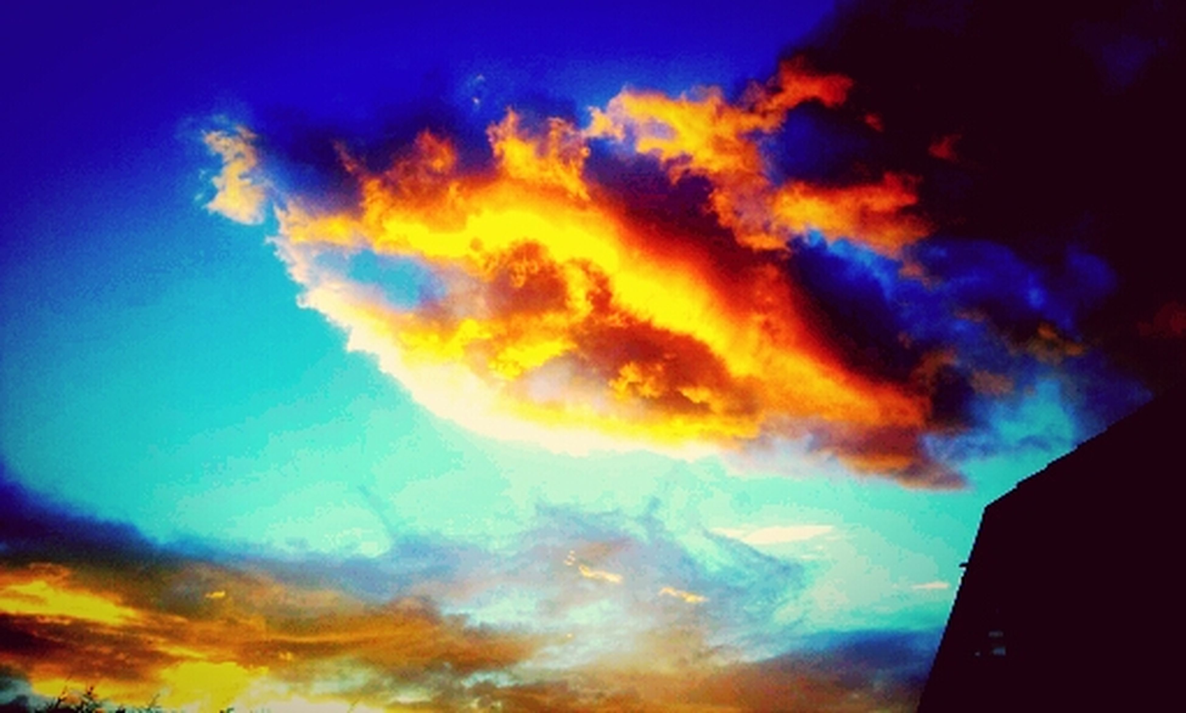 sky, low angle view, cloud - sky, cloudy, sunset, cloud, dramatic sky, beauty in nature, blue, nature, scenics, silhouette, cloudscape, weather, dusk, outdoors, tranquility, atmospheric mood, moody sky, building exterior