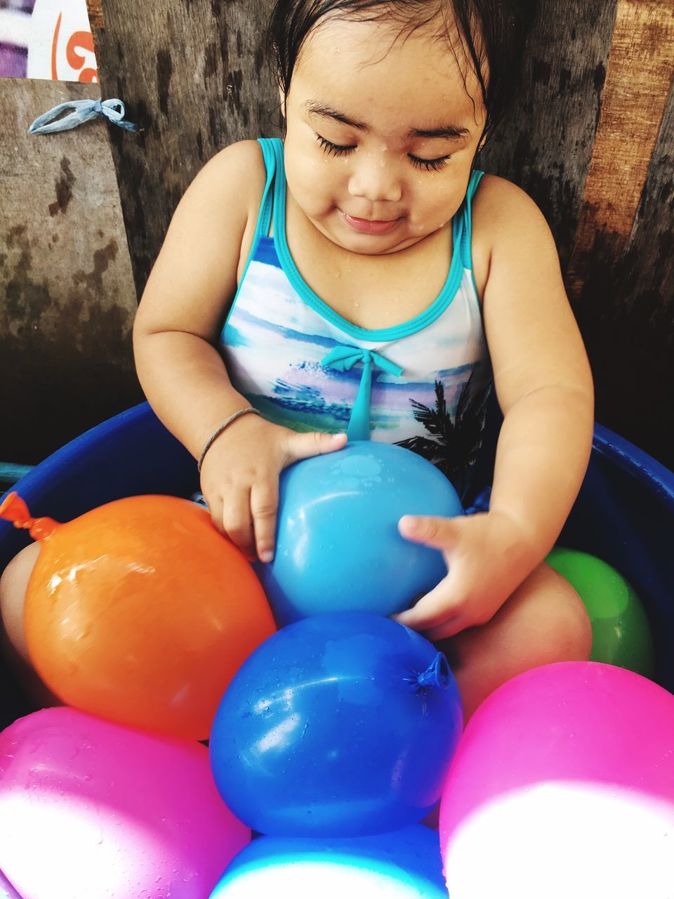 childhood, playing, real people, balloon, one person, blue, girls, happiness, fun, cute, leisure activity, smiling, multi colored, elementary age, boys, celebration, lifestyles, sitting, indoors, day, child, people