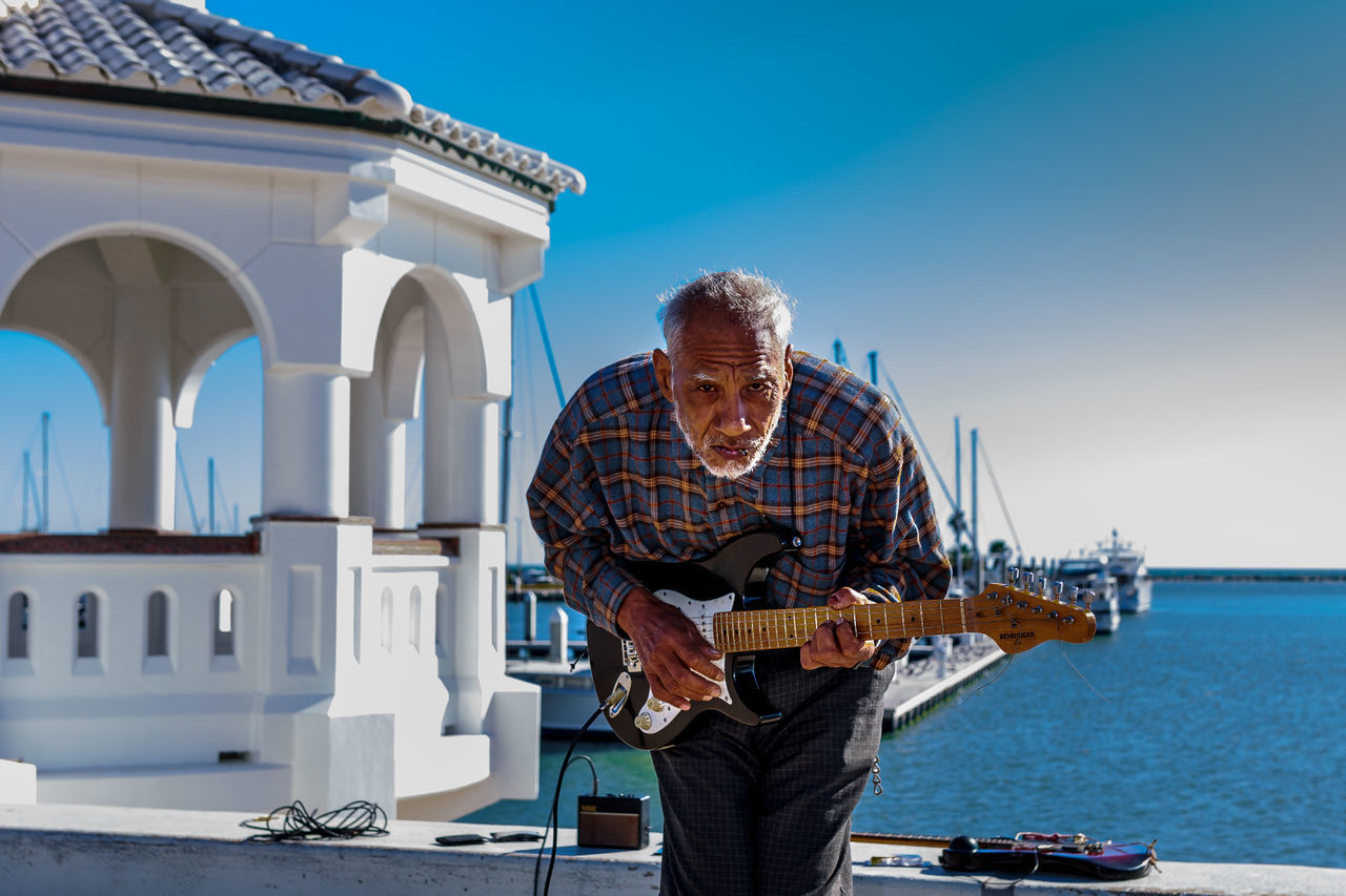 senior adult, senior men, one person, real people, leisure activity, front view, casual clothing, music, standing, guitar, day, holding, outdoors, lifestyles, musical instrument, clear sky, skill, sky, playing, gray hair, portrait, eyeglasses, one man only, only men, adult, adults only, people