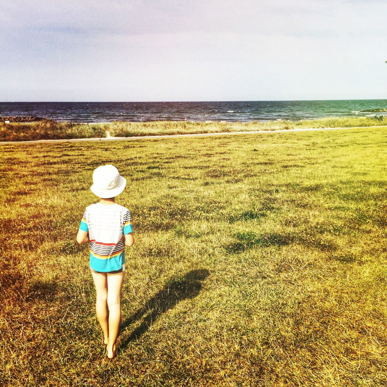 Summer View Summer Enjoying The Sun Kids Small boy is looking over meadow to the ocean