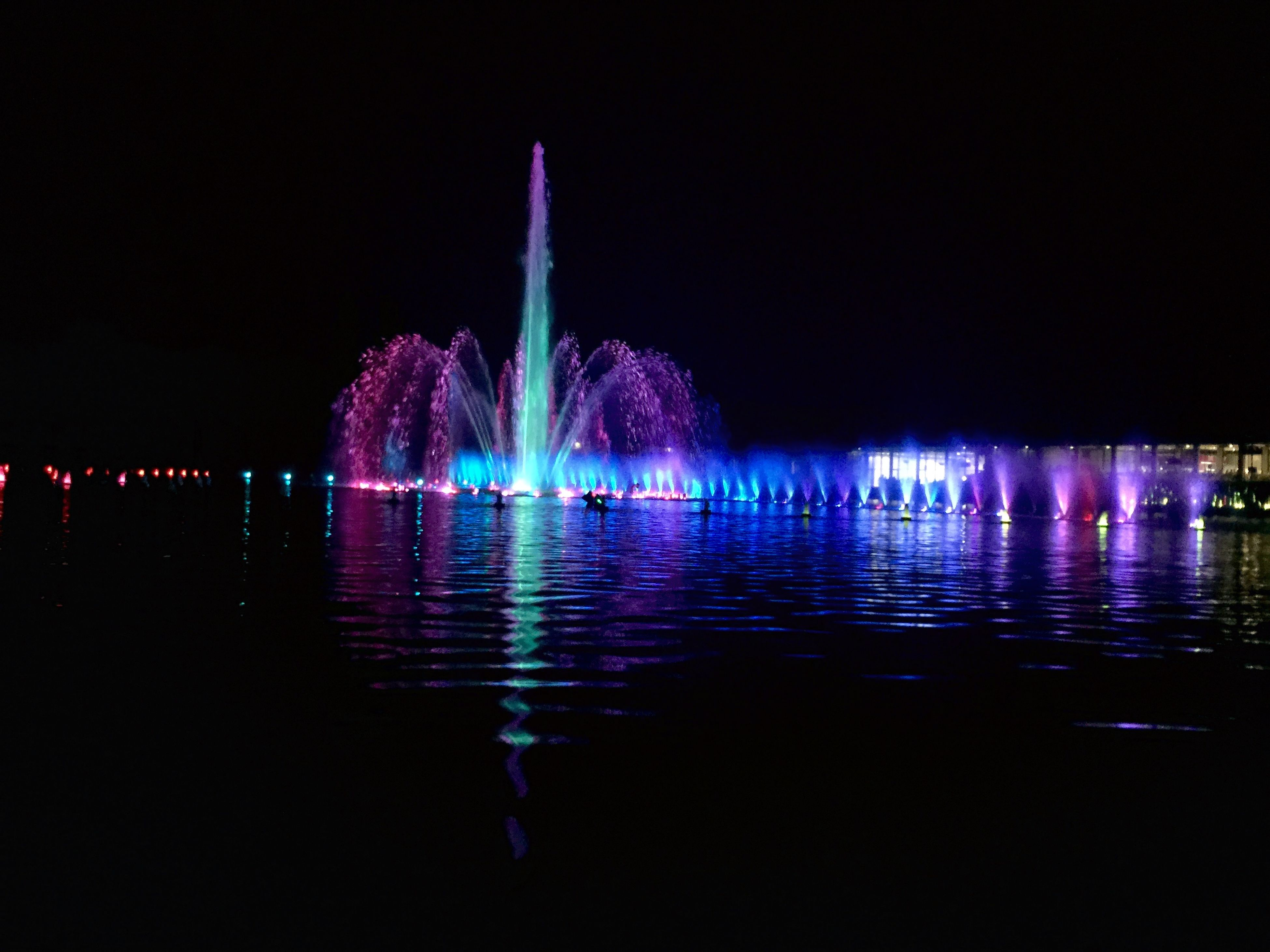 illuminated, night, water, reflection, long exposure, waterfront, building exterior, built structure, multi colored, clear sky, motion, architecture, glowing, fountain, firework display, copy space, city, river, sea, sky