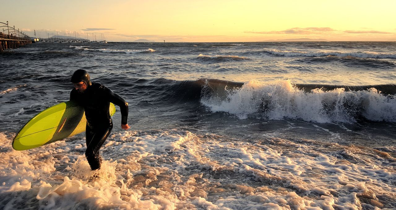 Sea Beach Wave Outdoors Real People Sunset Yellow Splashing One Person Water Men Only Men Horizon Over Water Aquatic Sport Nature Day Beauty In Nature Extreme Sports One Man Only People Dramatic Sky Cloudscape Ominous Environment Scenics