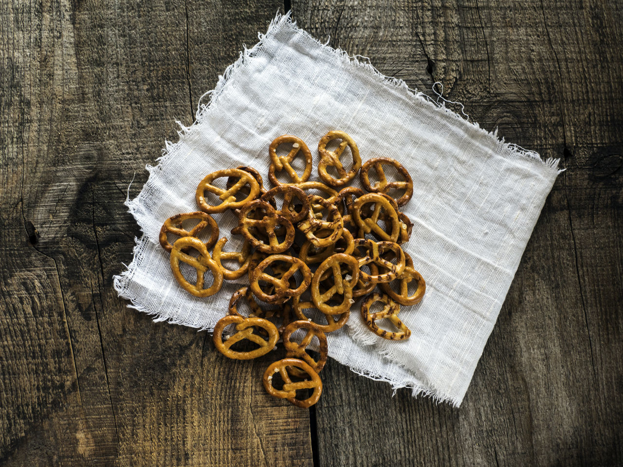 Heap of fresh Wheat salt pretzels on hessian linen fabric cloth and wooden table Cloth Collection Fabric Food And Drink Fresh Freshness Heap Hessian High Angle View Indoors  Large Group Of Objects Linen Pretzels Salt Spice Table Wheat Wooden