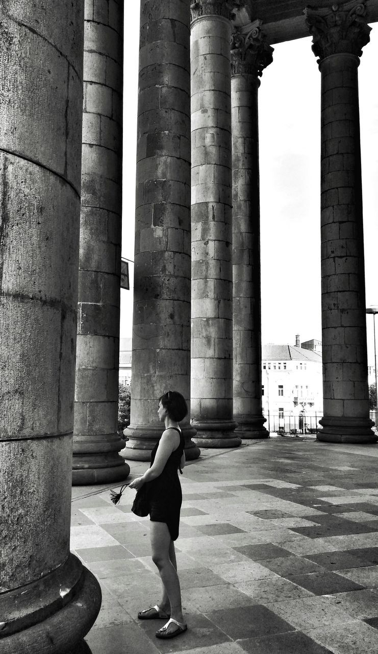 architectural column, real people, architecture, built structure, history, one person, casual clothing, full length, lifestyles, travel destinations, leisure activity, day, ancient, pillar, men, outdoors, adult, people