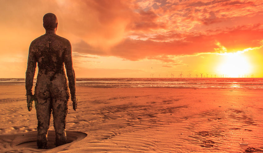 Another Place art installation by Anthony Gormley, on Crosby Beach near Liverpool at sunset Another Place Anthony Gormley Art Installation Cloud Crosby Beach Dramatic Sky Iron Man Liverpool Statue Algae Another Place By Anthony Gormley Art Beach Golden Hour Iron Men One Person Orange Color Outdoors Ripples In The Sand Sand Sea Statues Sun Sunset Water