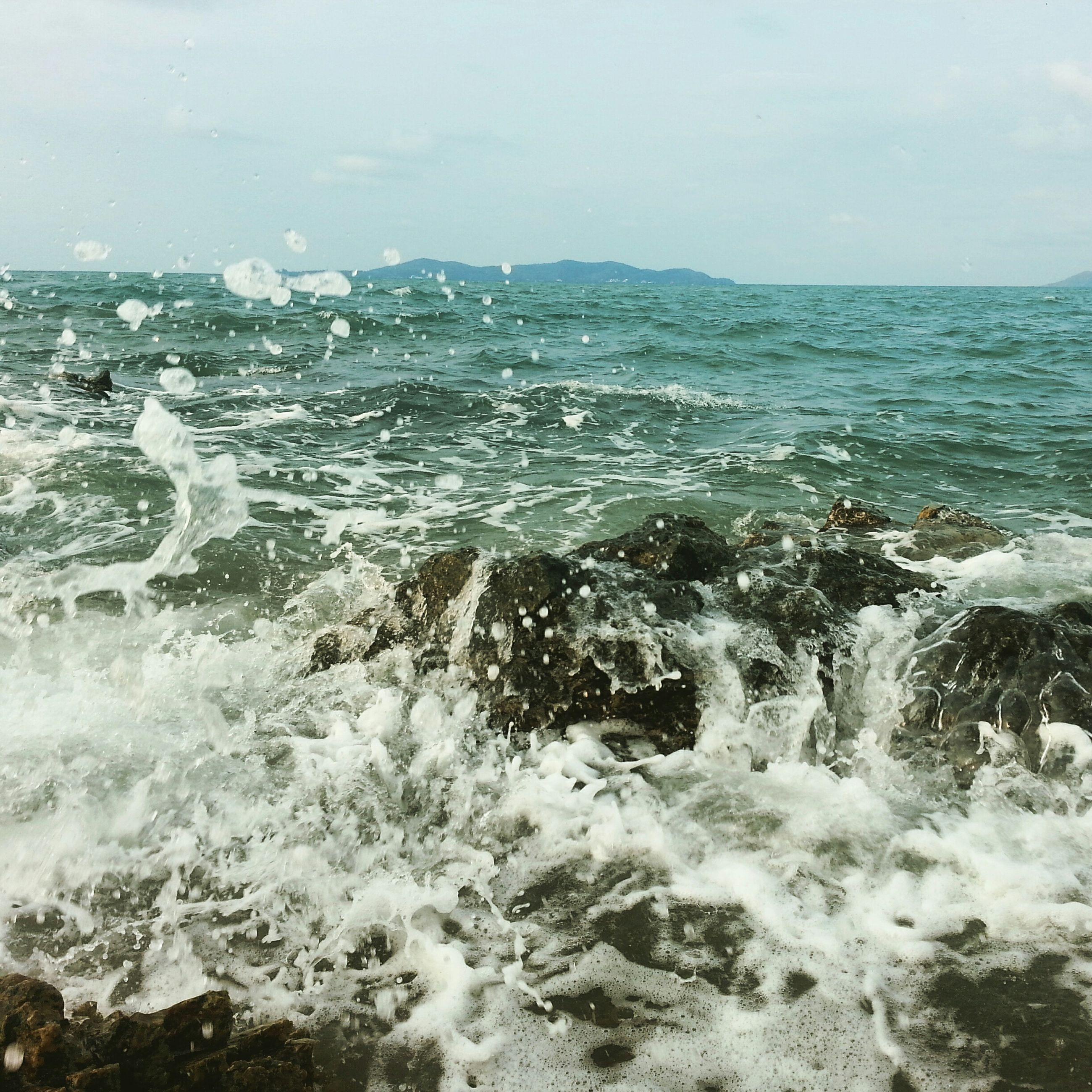 water, sea, wave, surf, horizon over water, scenics, motion, beauty in nature, splashing, nature, sky, tranquil scene, shore, waterfront, tranquility, power in nature, beach, rock - object, idyllic, day
