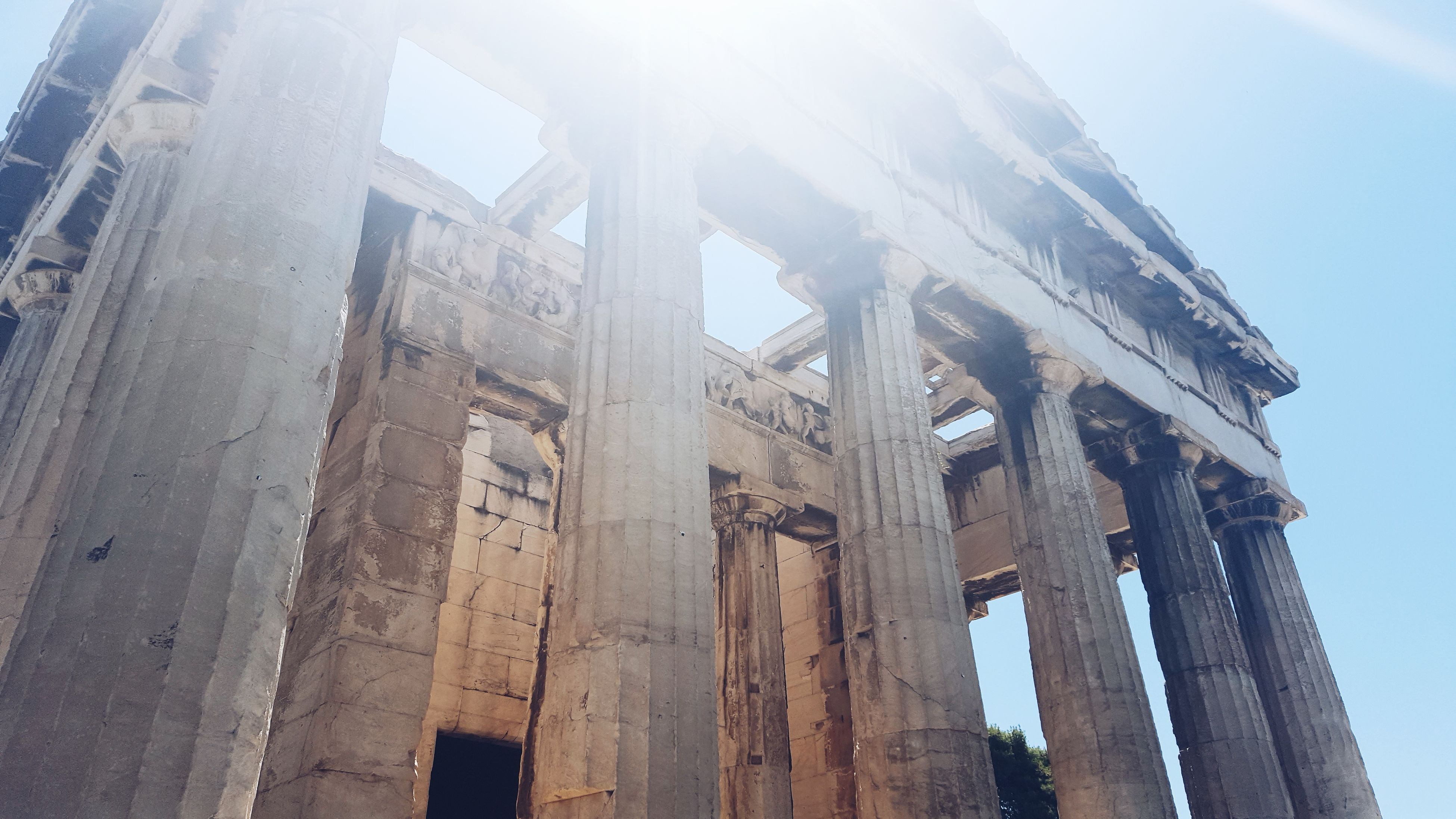 architecture, built structure, low angle view, building exterior, sky, history, sunlight, sunbeam, old, architectural column, sun, no people, day, outdoors, travel destinations, city, lens flare, famous place, building, old ruin
