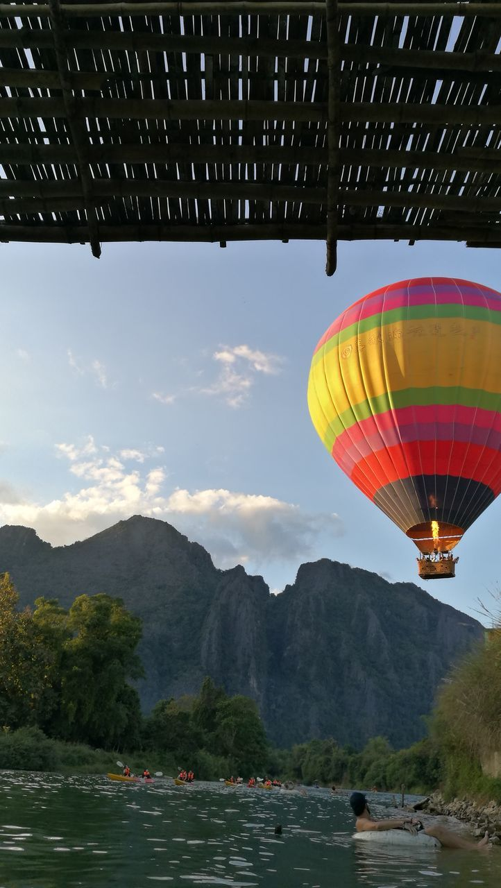 mountain, transportation, scenics, adventure, nature, mode of transport, hot air balloon, beauty in nature, day, outdoors, mountain range, sky, travel, flying, real people, mid-air, water, travel destinations, ballooning festival, nautical vessel, tree, parachute