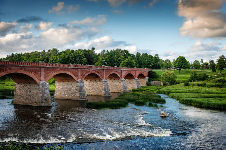 Old bridge with arches over the river. Arch Architecture Bridge - Man Made Structure Built Structure Cloud - Sky Connection Day Kuldiga Kuldīga, Latvija Latvia Latvia Riga Motion Nature No People Outdoors River Sky The Architect - 2017 EyeEm Awards Tree Water