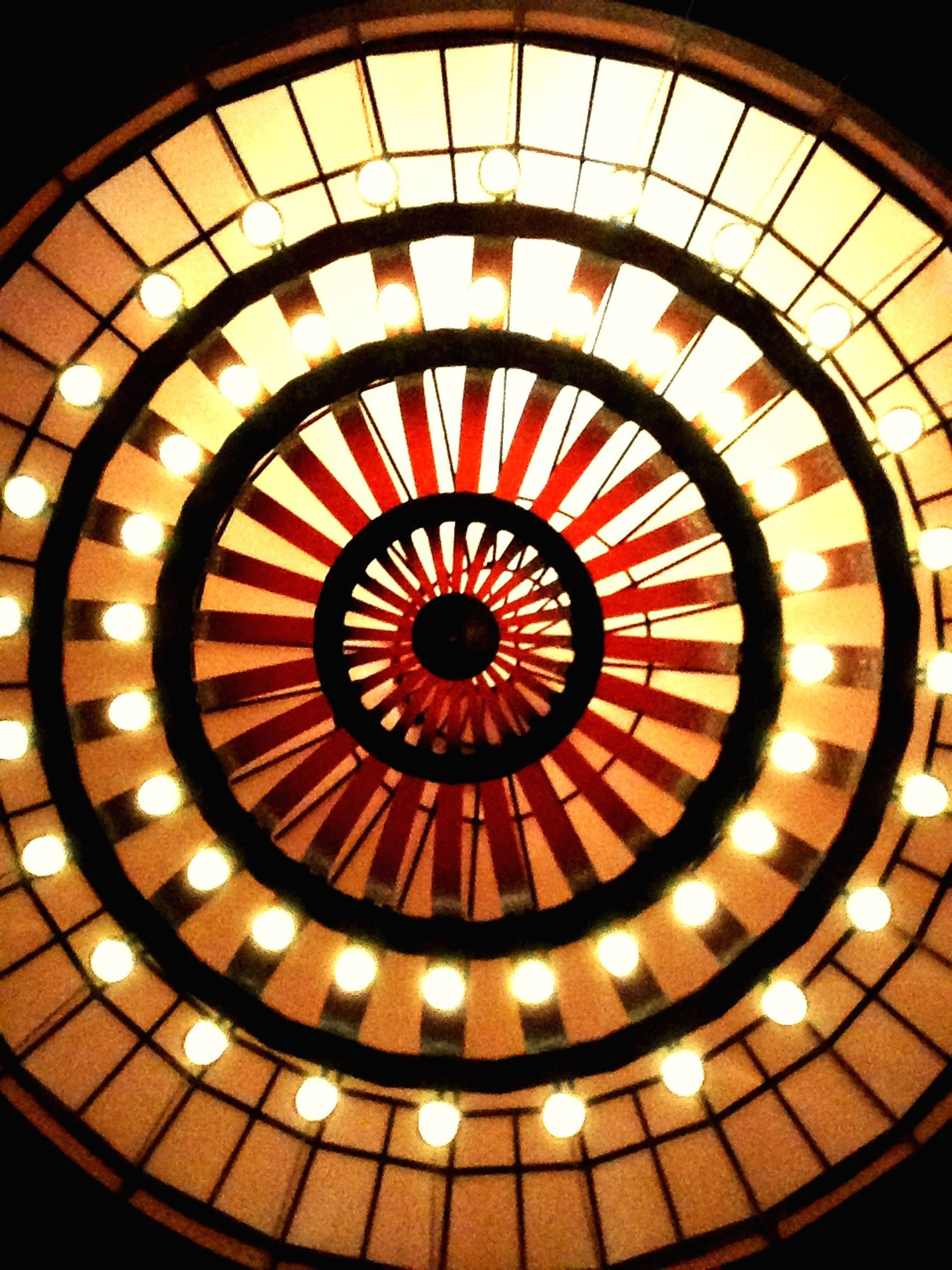 indoors, circle, ceiling, pattern, geometric shape, illuminated, design, full frame, backgrounds, lighting equipment, shape, directly below, no people, decoration, low angle view, yellow, built structure, repetition, glowing, orange color
