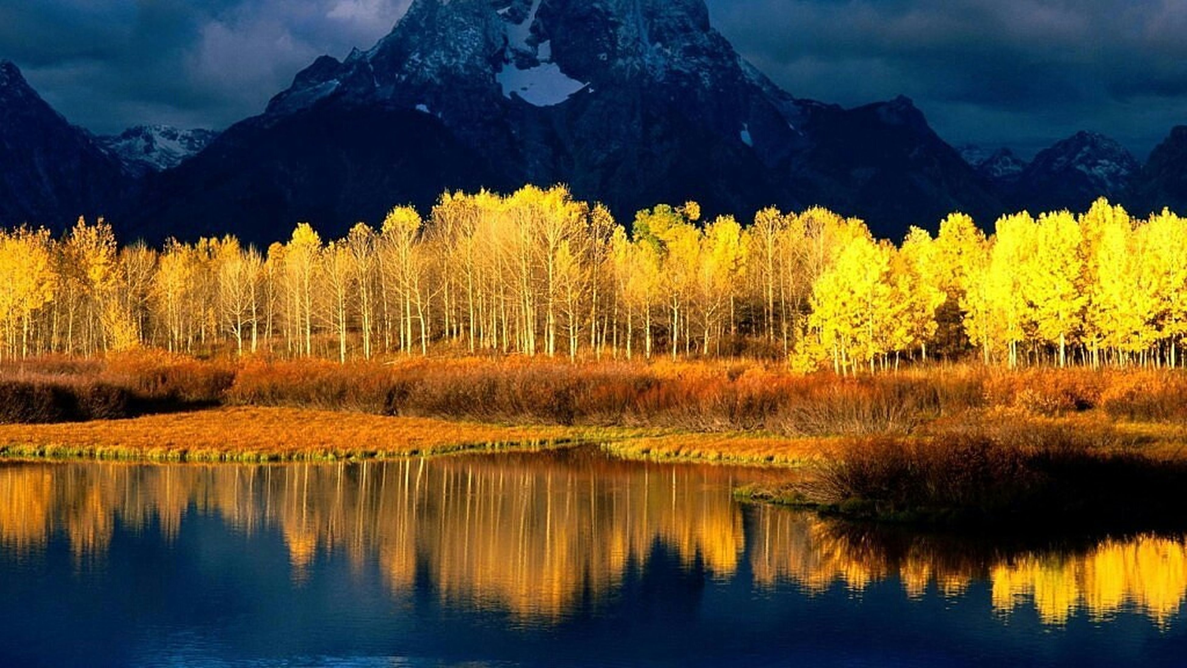water, mountain, tranquil scene, lake, beauty in nature, scenics, tranquility, reflection, nature, waterfront, sky, yellow, mountain range, idyllic, tree, growth, landscape, non-urban scene, river, no people