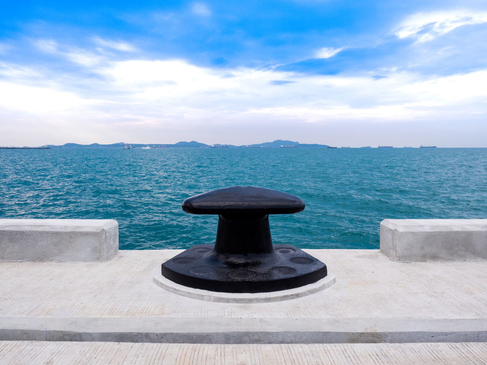The new mooring bollard to settle on the dock of concrete at port of thailand Sea Water Cloud - Sky Horizon Over Water Day Sky Tranquility Scenics Nature No People Sand Beach Outdoors Beauty In Nature bollard Alongside Berth Harbor Boat Iron Jetty, Pier Knot LINE Marina Maritime Moor