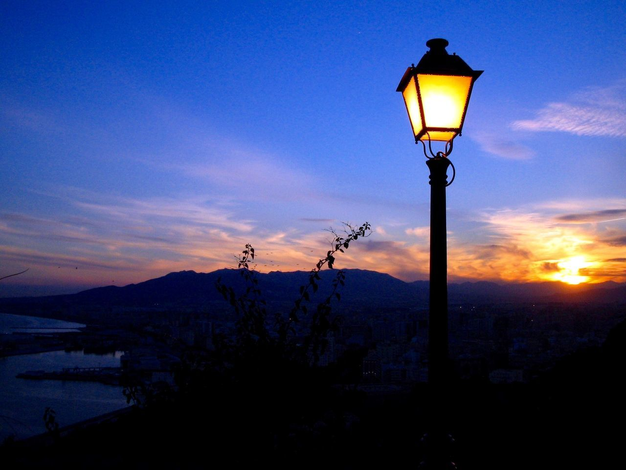 lighting equipment, silhouette, sunset, street light, nature, illuminated, sky, beauty in nature, outdoors, no people, tranquility, scenics, blue, mountain, day