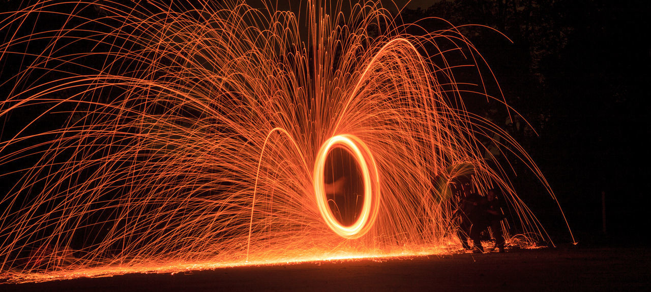 motion, long exposure, wire wool, night, spinning, illuminated, blurred motion, burning, glowing, light painting, circle, speed, danger, heat - temperature, light effect, swirl, one person, flame, real people, fireball, performance, outdoors, nature, people