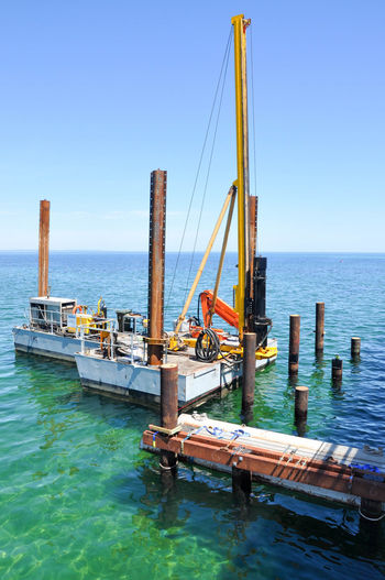 Construction platform putting in ocean pilings in the Indian Ocean in Busselton, Western Australia Beams Blue Busselton Clear Sky Construction Day Equipment Horizon Over Water Indian Ocean Industrial Material Nature Ocean Pilings Outdoors Pilings Platform Posts Rusty Sea Seascape Sky Turquoise Water Western Australia Wood