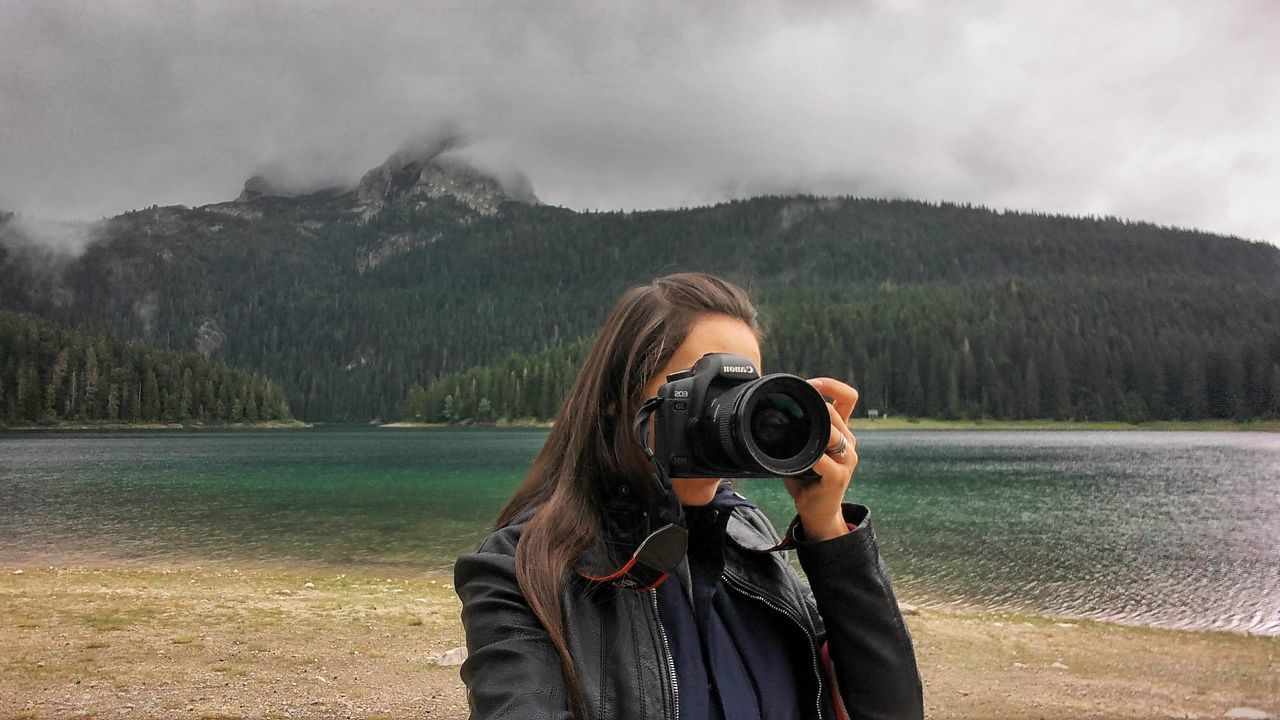Woman travel with photo camera near lake with mountain view. Rainy weather. Caucasian woman with long hair. Adult Adults Only Beauty In Nature Camera - Photographic Equipment Day Digital Camera Digital Single-lens Reflex Camera Lake View Leisure Activity Mountain Mountain Range Nature One Person One Woman Only Only Women People Photographer Photographing Photography Themes Scenics Selfie SLR Camera Technology Vacations Women