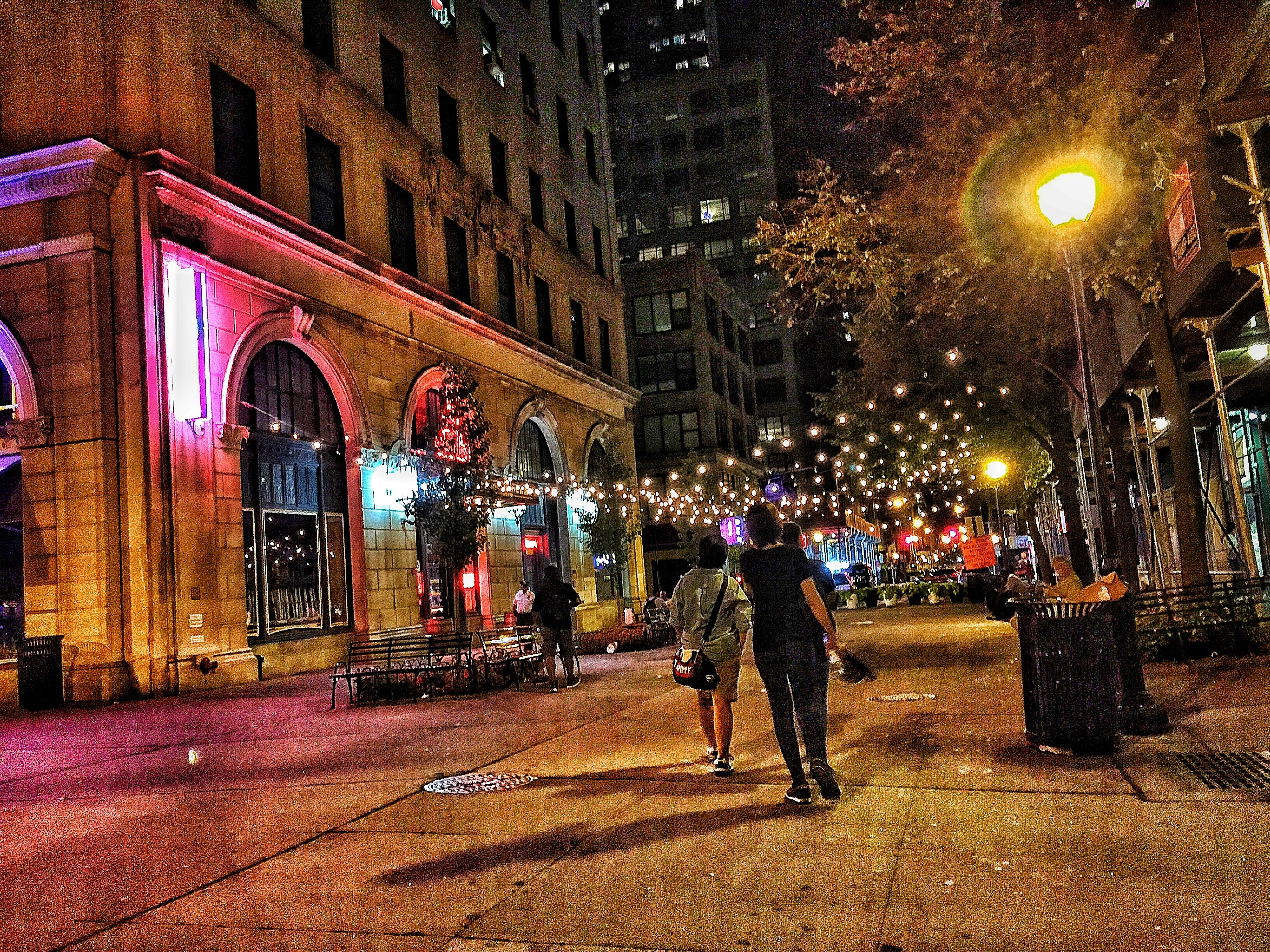 lifestyles, leisure activity, illuminated, person, men, night, architecture, large group of people, building exterior, full length, built structure, rear view, celebration, walking, togetherness, lighting equipment, standing, casual clothing, tree