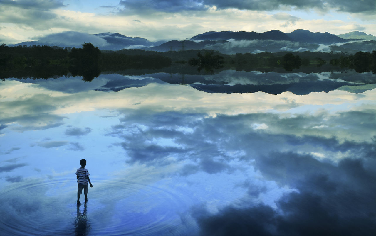 Boy walking in peace lake concept art Adventure Beauty In Nature Cloud - Sky Day Distant Full Length Idyllic Lake Landscape Looking At View Mountain Mountain Range Nature One Person Outdoors People Rear View Reflection Scenics Sky Standing Tranquil Scene Tranquility Water