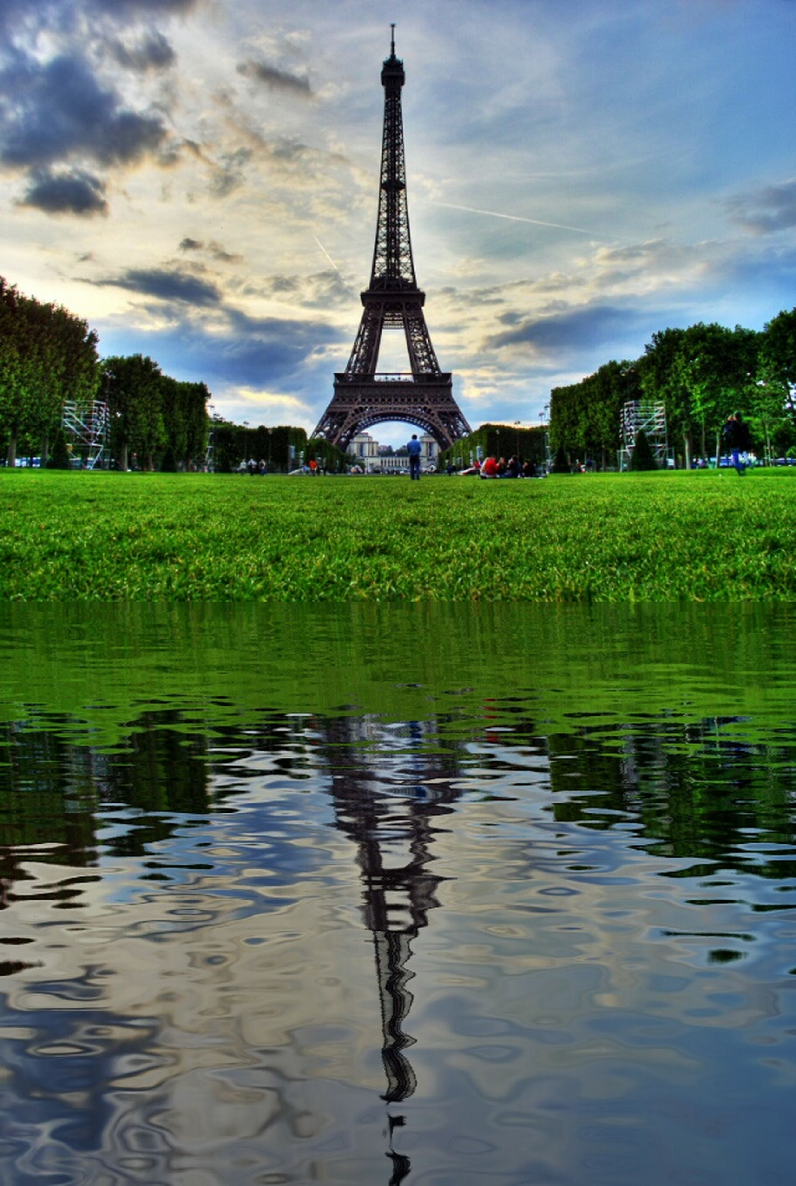 architecture, sky, built structure, water, building exterior, tree, cloud - sky, reflection, grass, tower, travel destinations, river, waterfront, famous place, cloud, green color, cloudy, lake, history, tourism